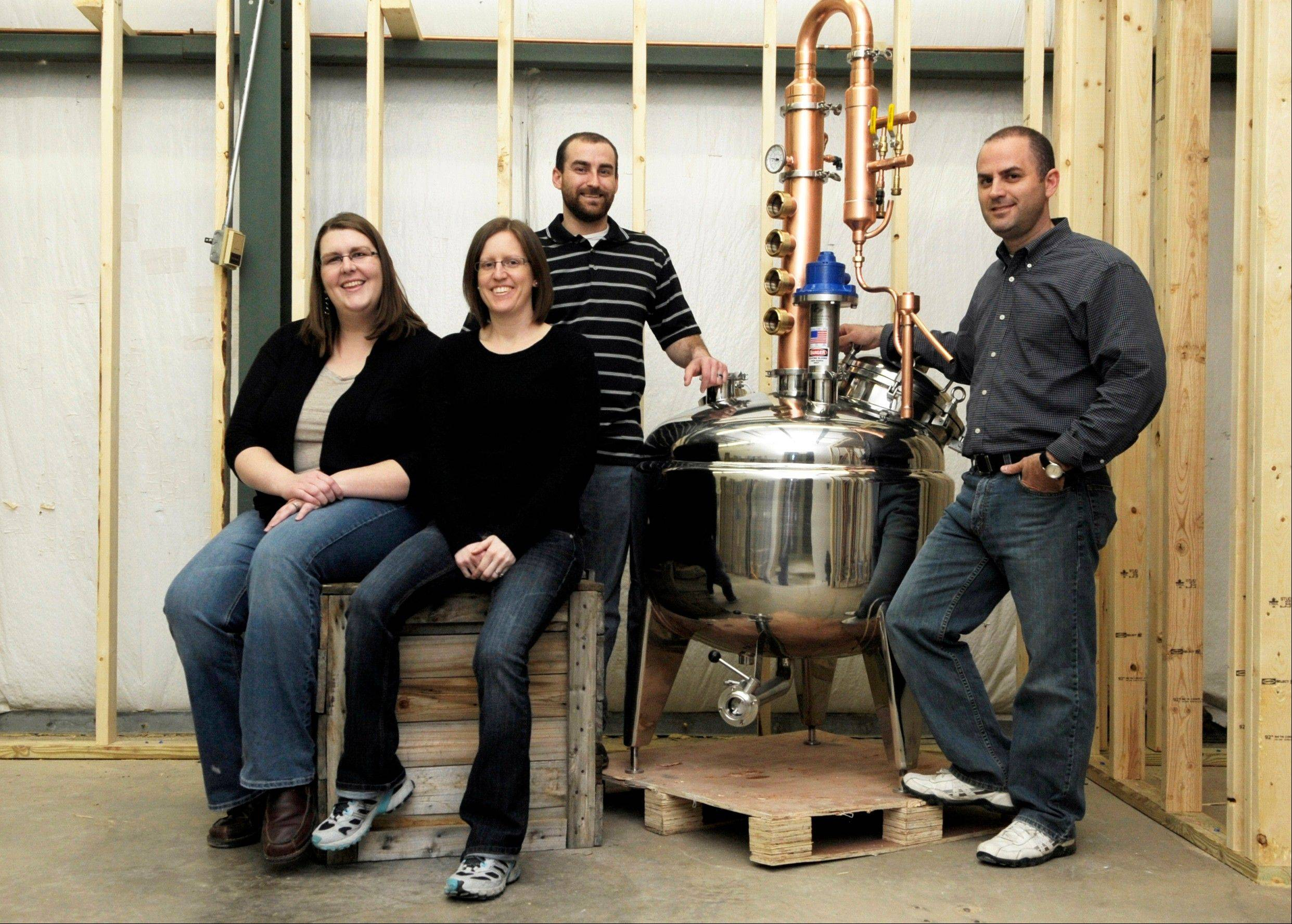 From left, sister-in-laws Kassi and Kristin Williams with brothers Jesse and Jon Williams in front of their 60-gallon whiskey still in the building still under construction that will house J.K. Williams Distilling in East Peoria.