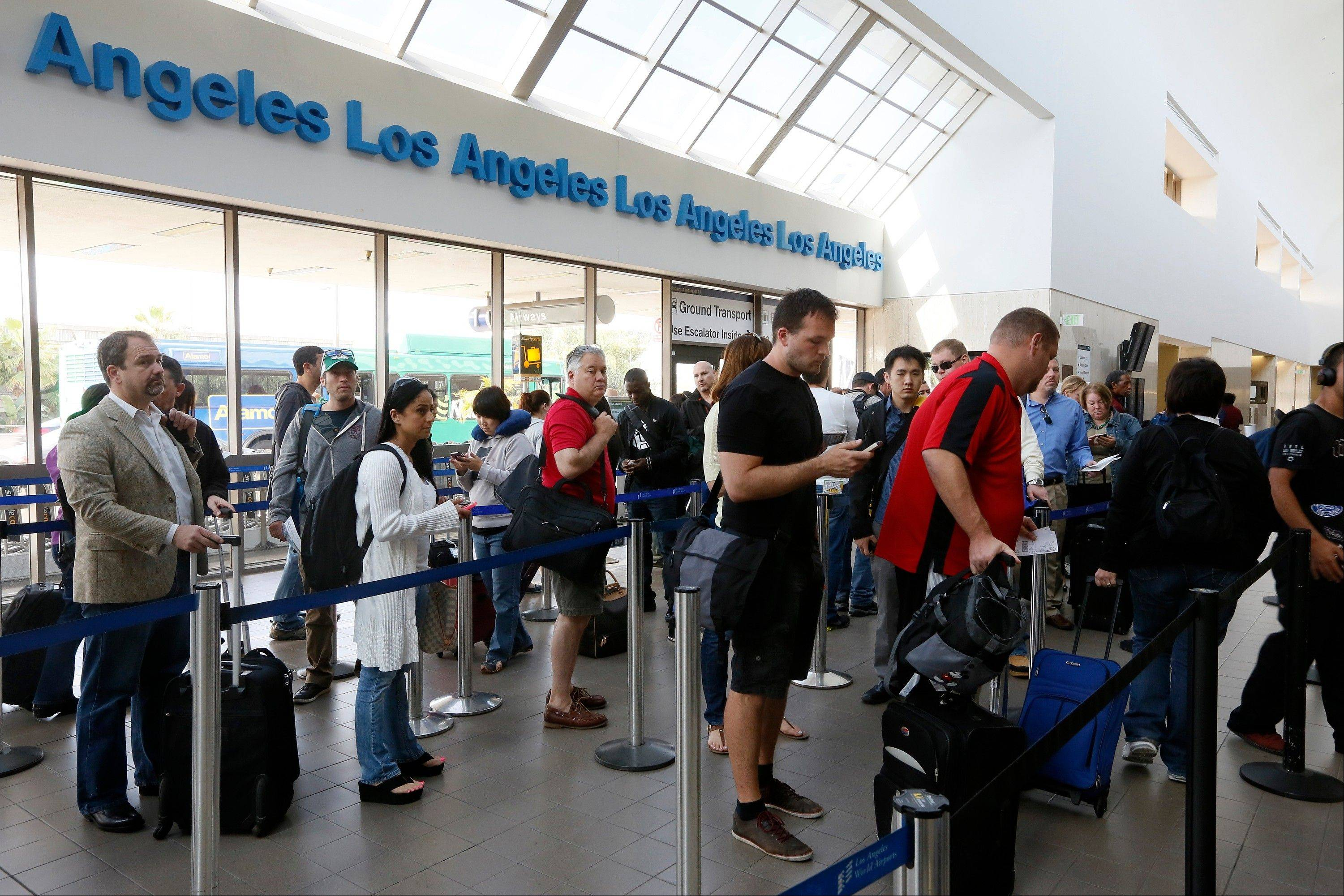 Travelers stand in line Monday at the LAX International Airport in Los Angeles.