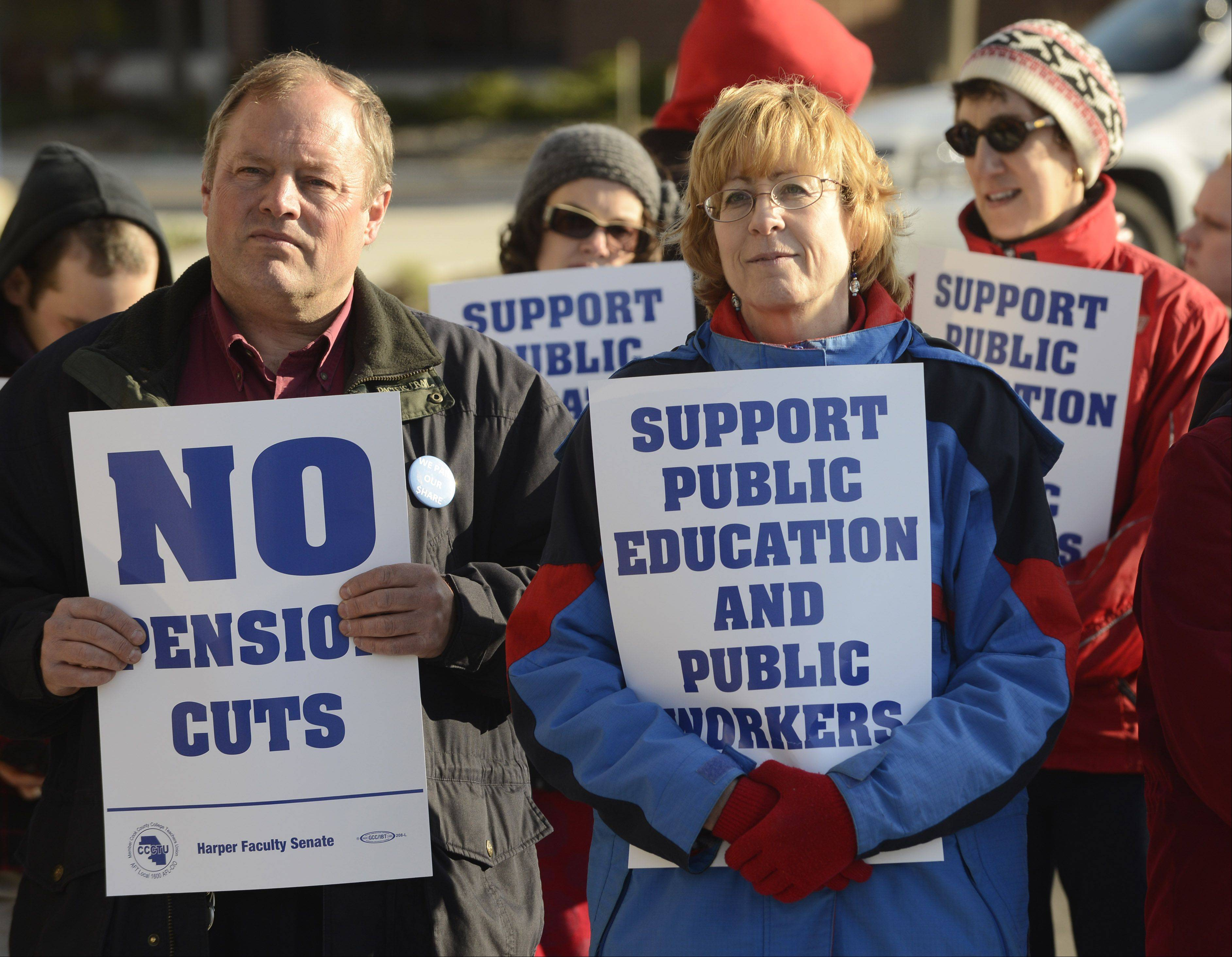 Retired Harper College teacher Randy Schietzelt, left, and current faculty member Virginia Turner hold their signs while protesting outside before the pension reform forum Wednesday night at Harper.