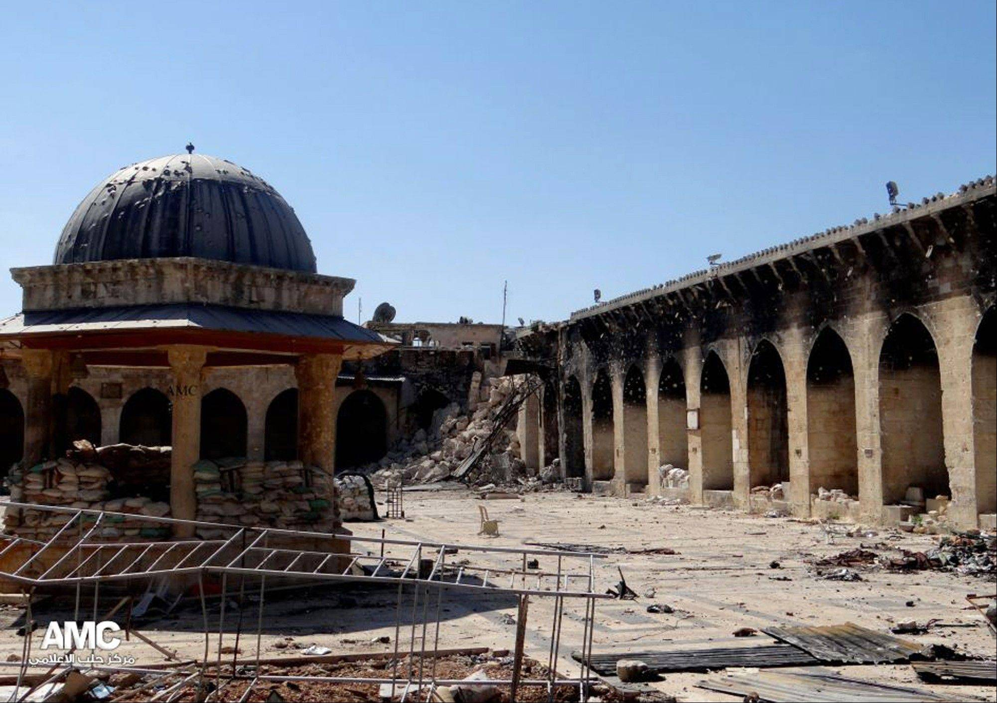 The damaged famed 12th century Umayyad mosque without the minaret, background right corner, which was destroyed by the shelling, in the northern city of Aleppo, Syria, Wednesday April 24, 2013. The minaret of a famed 12th century Sunni mosque in the northern Syrian city of Aleppo was destroyed Wednesday, leaving the once-soaring stone tower a pile of rubble and twisted metal scattered in the tiled courtyard.