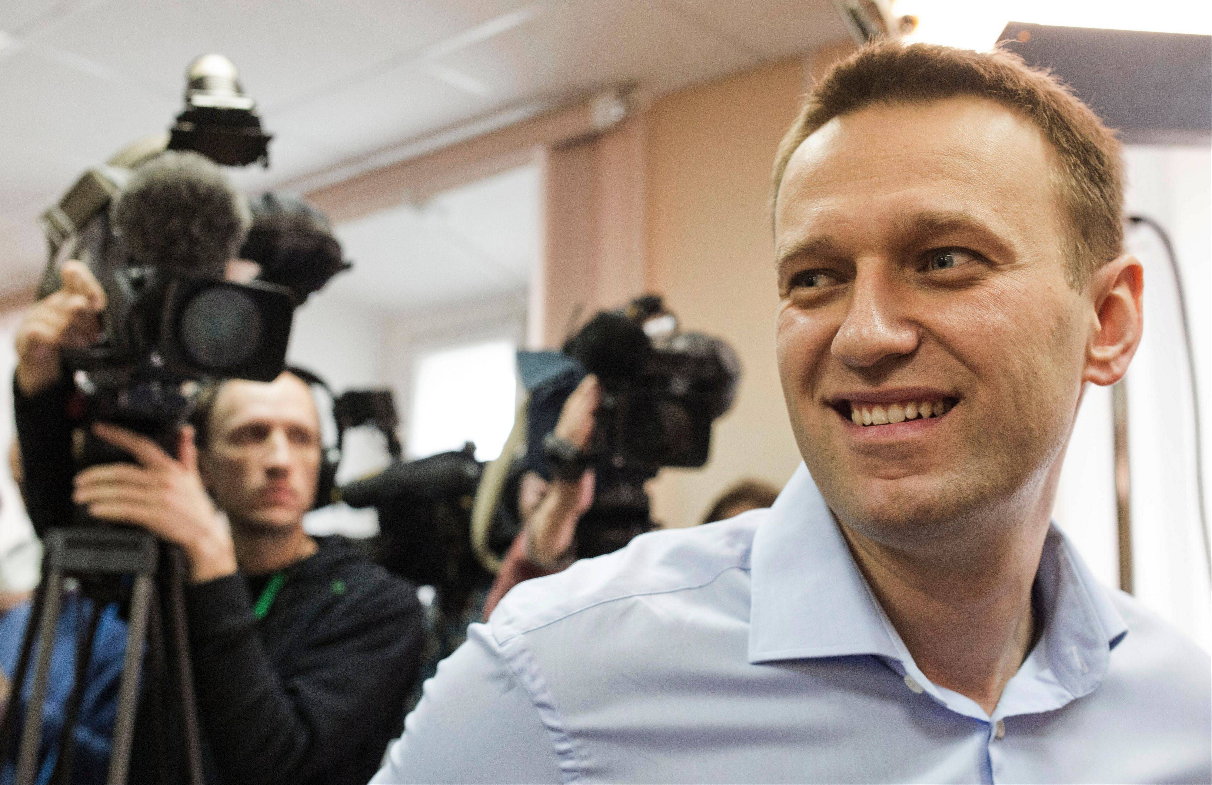 Russian opposition leader Alexei Navalny smiles in a courtroom as he attends a trial in Kirov, Russia, Wednesday, April 24, 2013. The trial has resumed in the case against a Russian opposition leader who led protests against President Vladimir Putin and exposed alleged corruption in his government. Navalny is accused of heading an organized criminal group that embezzled $500,000 worth of timber from a state-owned company.