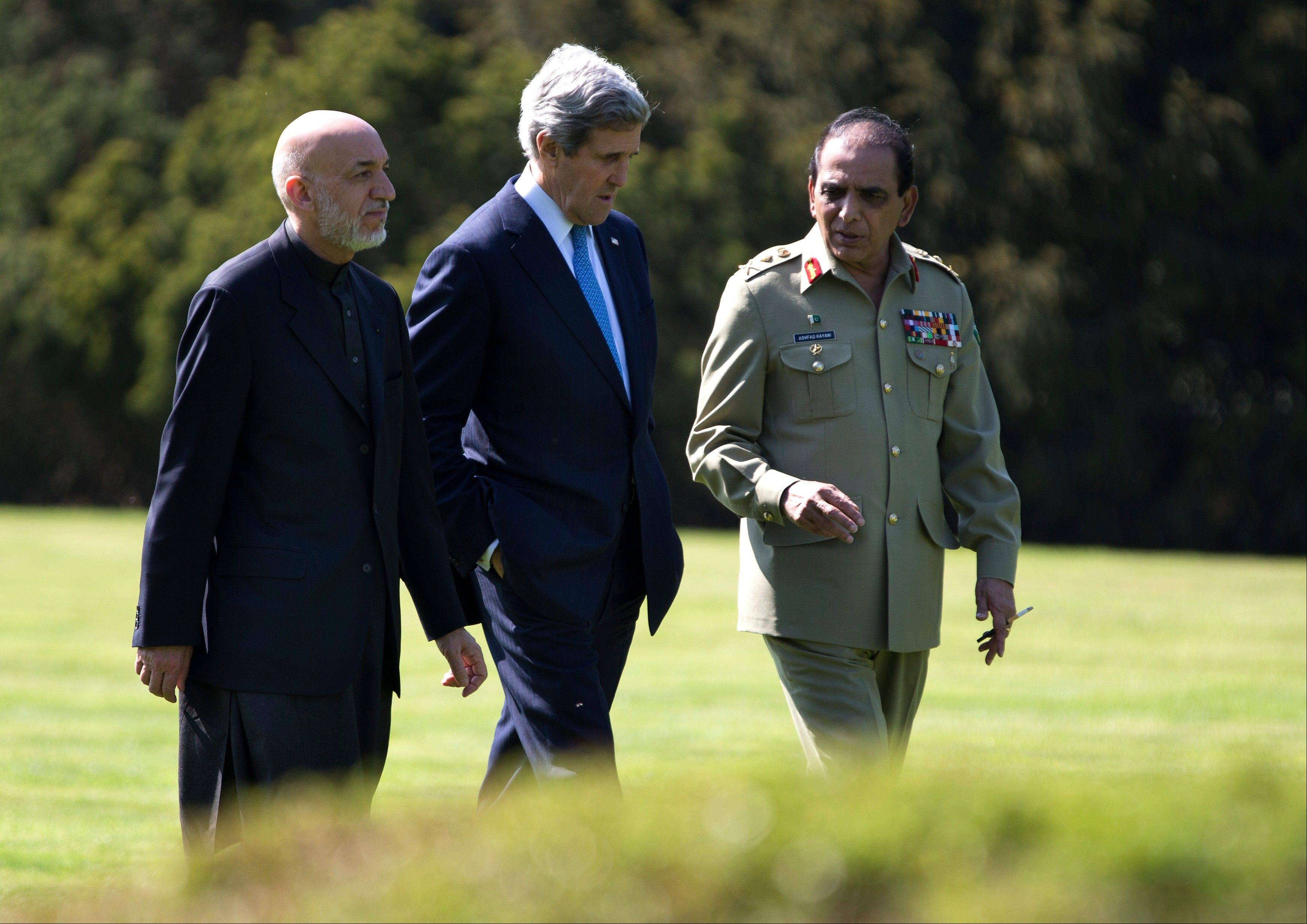U.S. Secretary of State John Kerry, center, talks with Afghan President Hamid Karzai, left, and Pakistani Army Chief Gen. Ashfaq Parvez Kayani as they take a walk during a break in a meeting on Wednesday, April 24, 2013, in Brussels, Belgium. The trilateral meeting is to discuss regional security issues, and the 2014 withdrawal of NATO combat forces from Afghanistan.