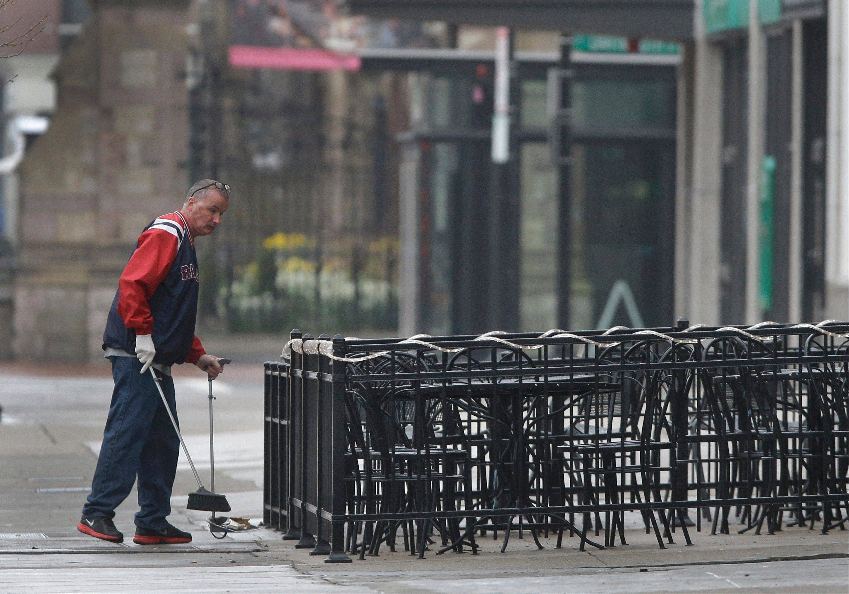 A man sweeps around the outdoor seating area at a business on Boylston Street in Boston Tuesday, April 23, 2013 about two blocks from the Boston Marathon finish line where two bombings killed three people and injured many. Boylston Street businesses near the finish area remain closed to the public, but business owners are slowly being allowed to prepare to reopen.
