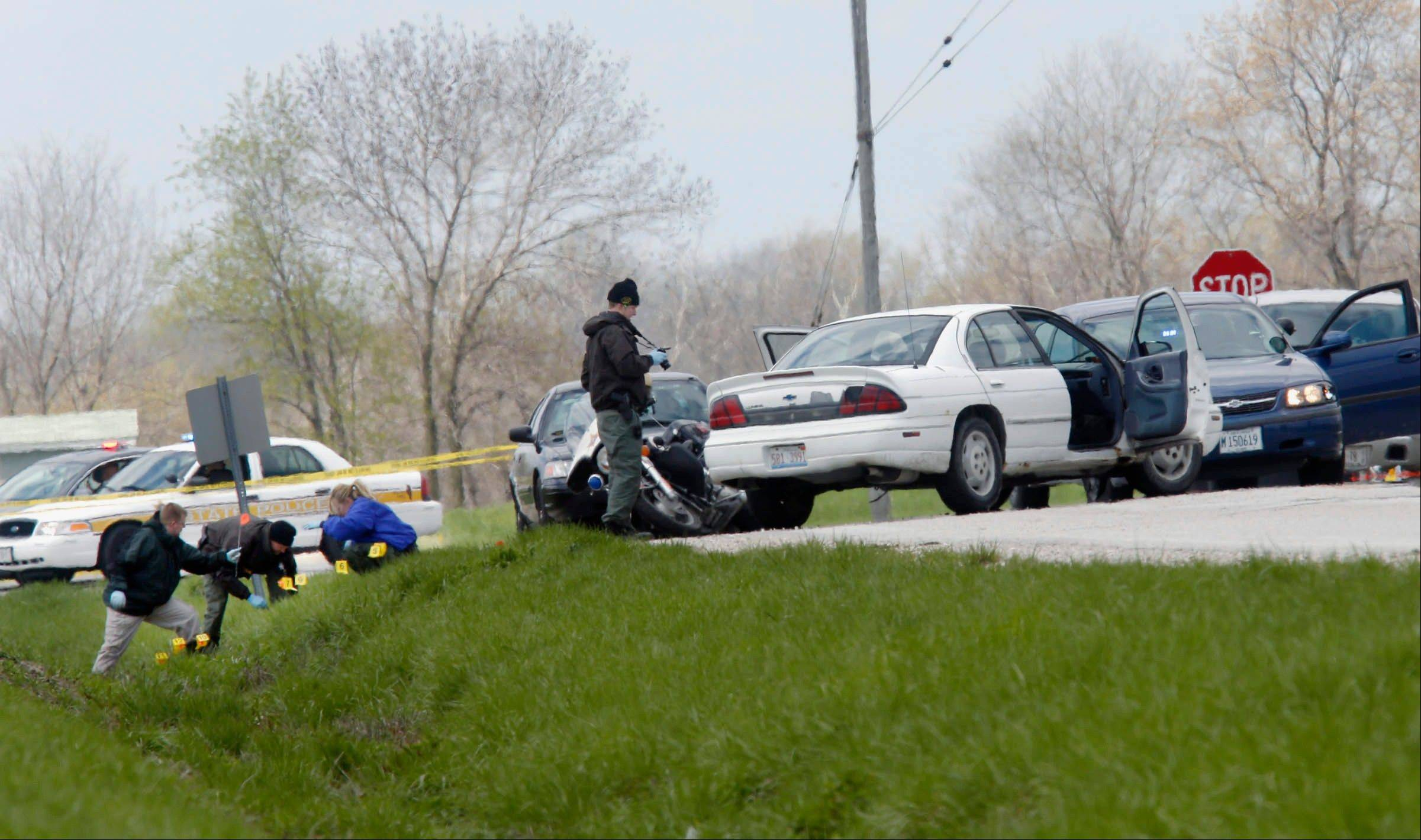 Illinois State Police process the scene Wednesday near Winchester, where a suspect wanted in the deaths of five people in nearby Manchester, was wounded after a car chase and an exchange of gunfire with law enforcement. The suspect, who was driving the white sedan, died later at a hospital.