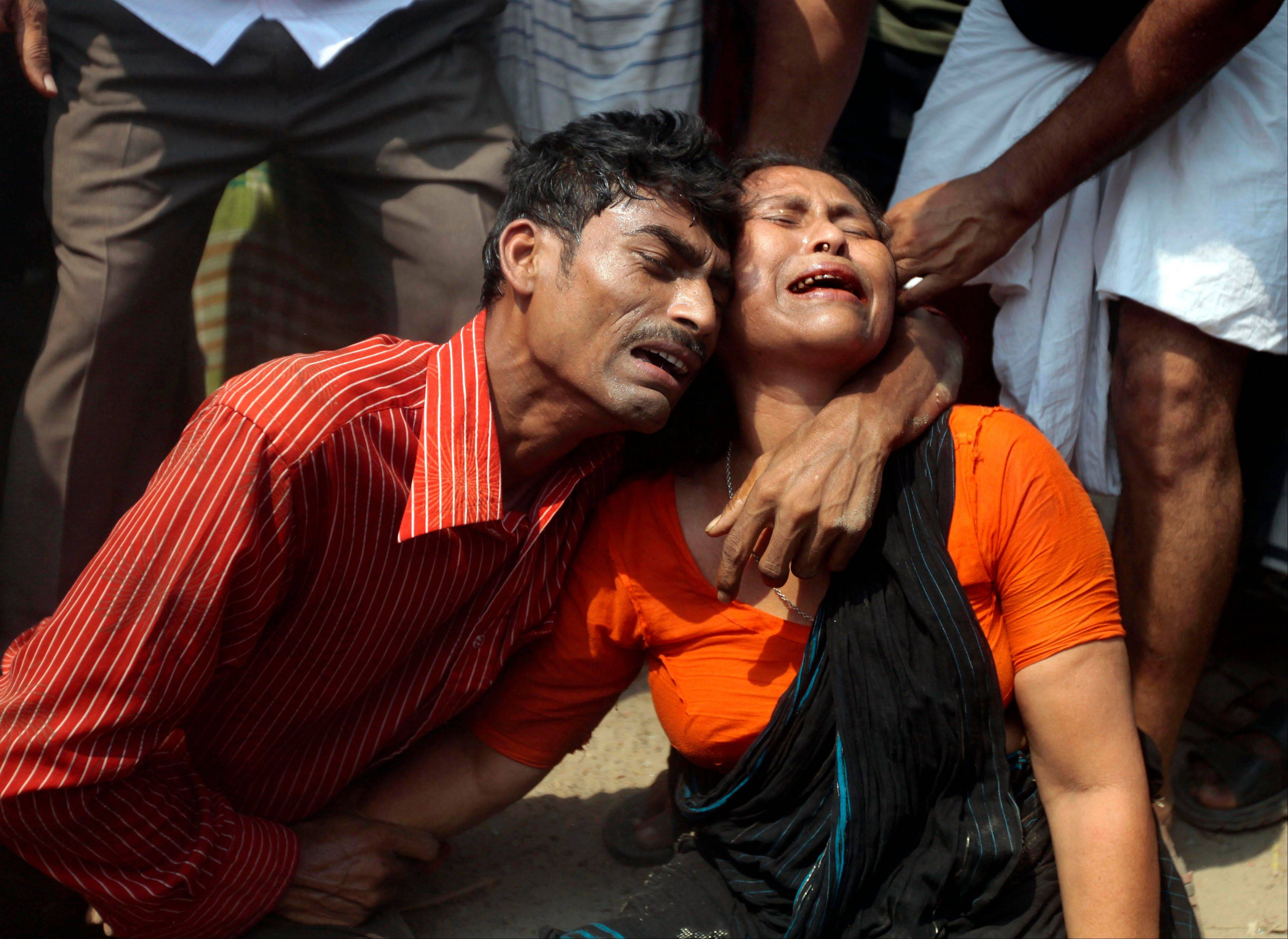 Relatives mourn a victim at the site where an eight-story building housing several garment factories collapsed in Savar, near Dhaka, Bangladesh, Wednesday, April 24, 2013. The building collapsed near Bangladesh's capital Wednesday morning, killing dozens of people and trapping many more in the rubble, officials said.