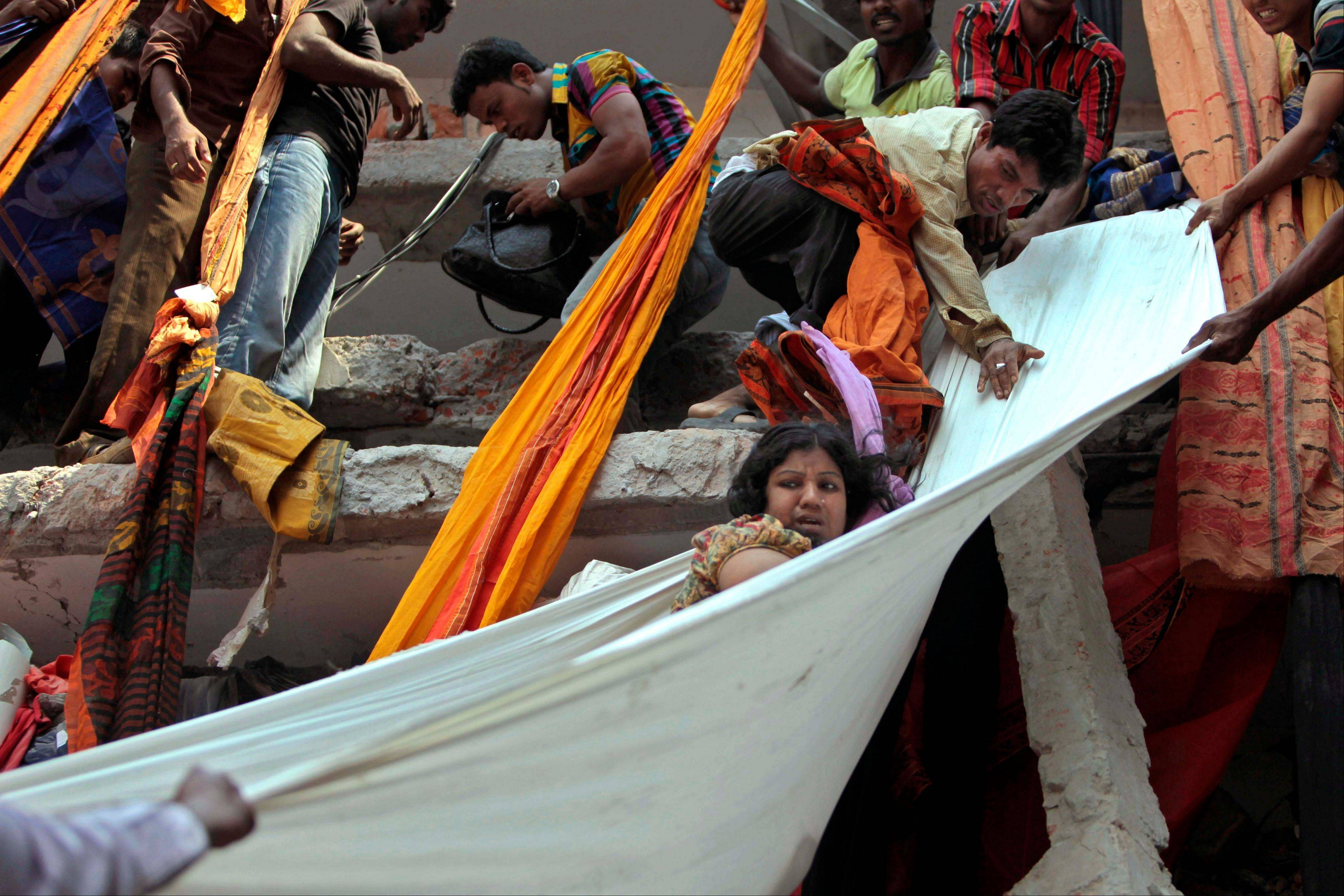 Rescue workers use pieces of clothes to bring down a survivor after an eight-story building housing several garment factories collapsed in Savar, near Dhaka, Bangladesh, Wednesday, April 24, 2013. The building collapsed near Bangladesh's capital Wednesday morning, killing dozens of people and trapping many more in the rubble, officials said.