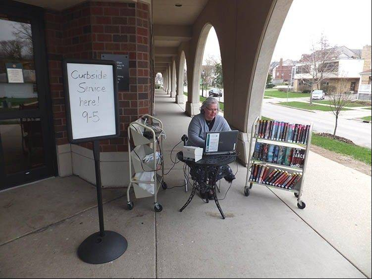 Glen Ellyn Public Library staff members are providing curbside service at the building's entrance this week while crews continue to clean up inside following last week's flood.