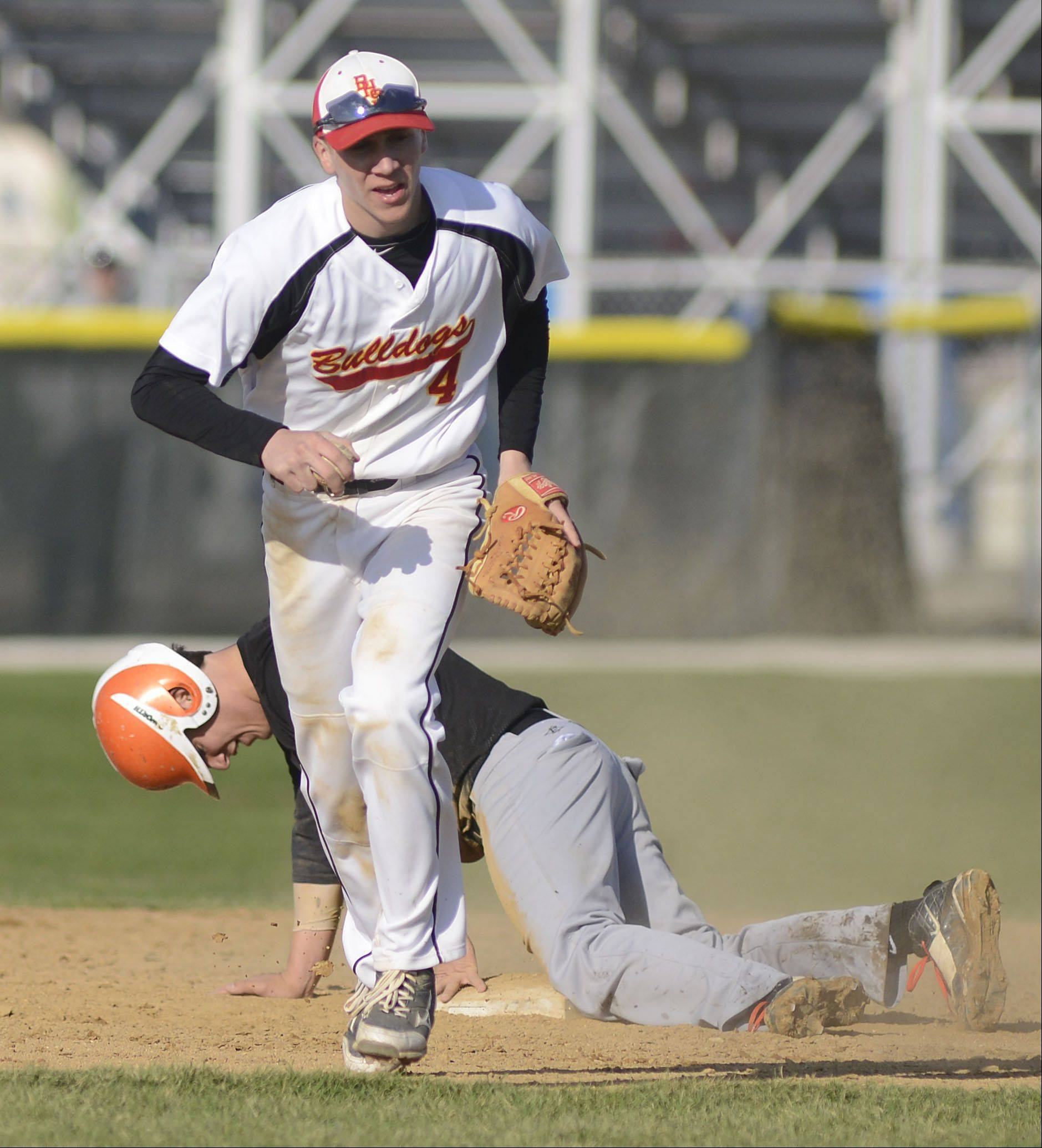 Batavia's Billy Zwick heads back to the dugout as St. Charles East's Anthony Sciarrino hangs his head after being tagged out at second base by Zwick in the fourth inning on Wednesday, April 24.