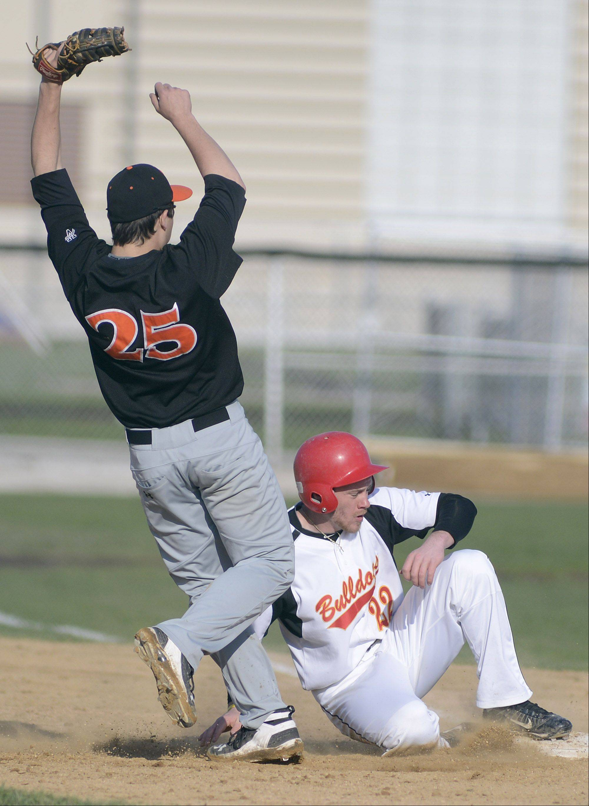 Batavia's Robbie Bowman slides into second base after being tagged out by St. Charles East's Brian Sobieski, ending a chase between first and second bases in the fourth inning on Wednesday, April 24.