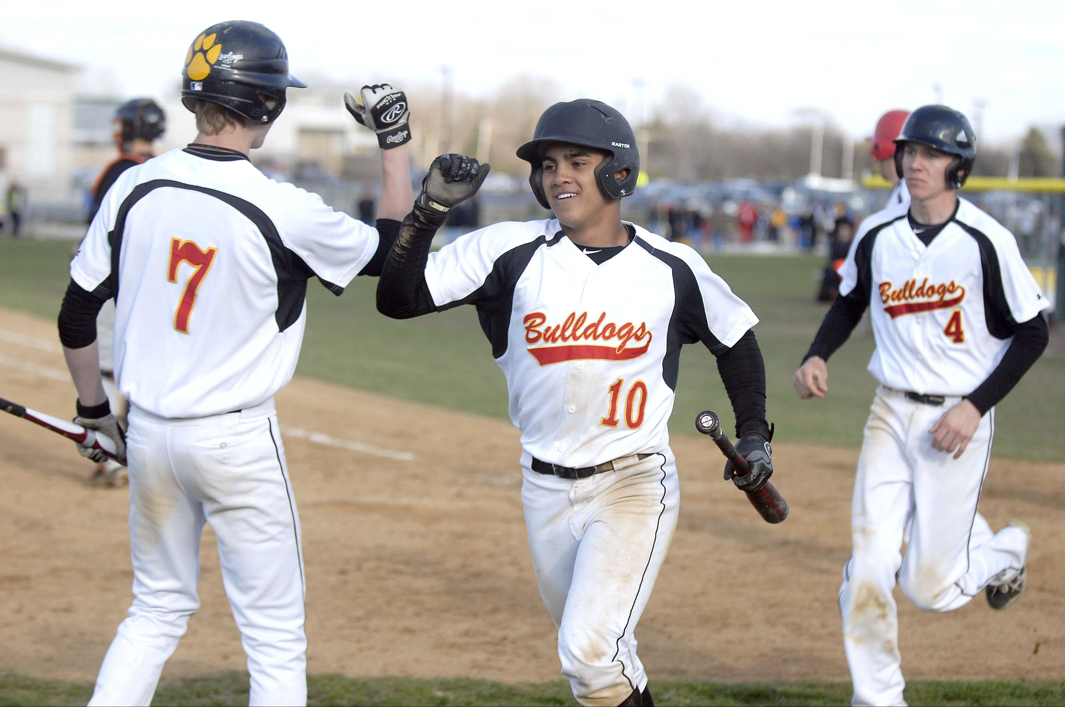 Batavia's Laren Eustace (10) and Billy Zwick (4) receive congrats from teammate Andrew Seigler after both scored in the fifth inning on Wednesday in Batavia.