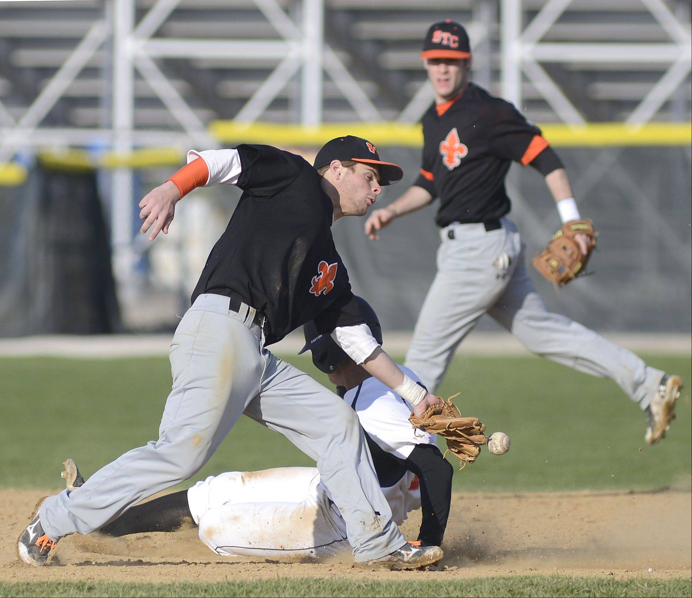 Batavia's Laren Eustace slips past St. Charles East's Nicholas Erickson and the ball to land safely on second base in the fifth inning on Wednesday, April 24.