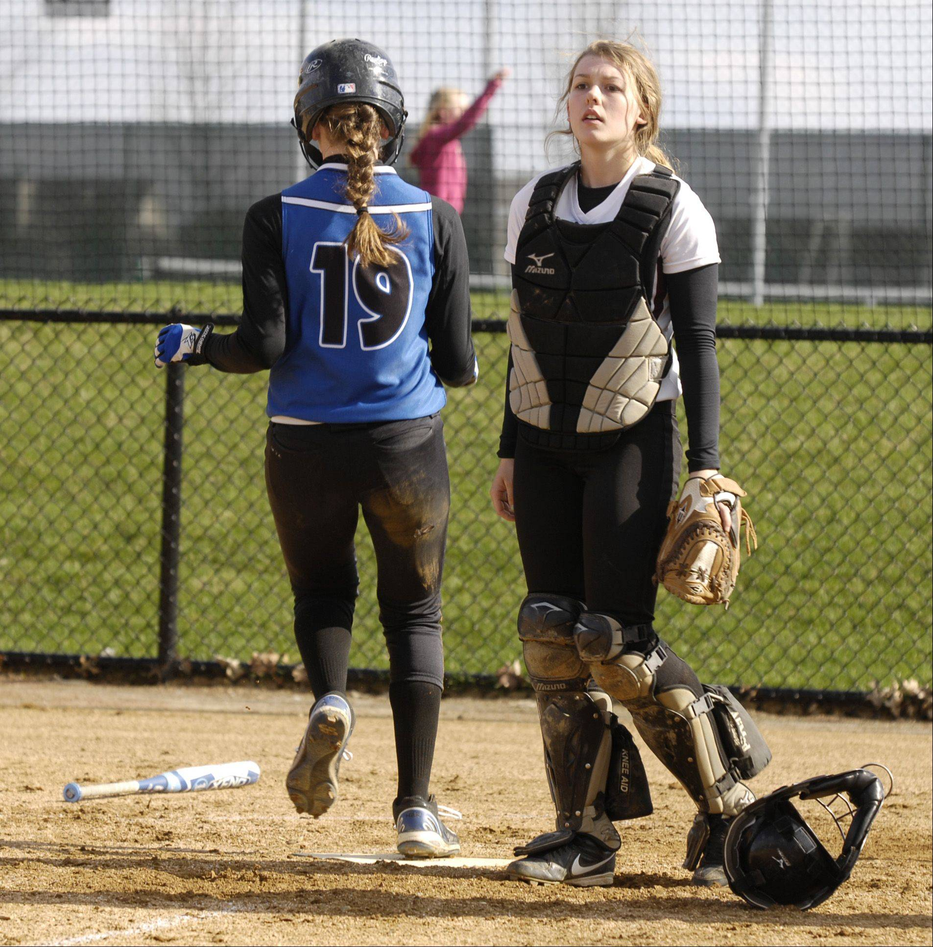AIi Dittrich of St. Francis scores one of the Spartans 15 runs, as Wheaton Academy catcher Jessica Rosse looks on, in West Chicago, Wednesday.