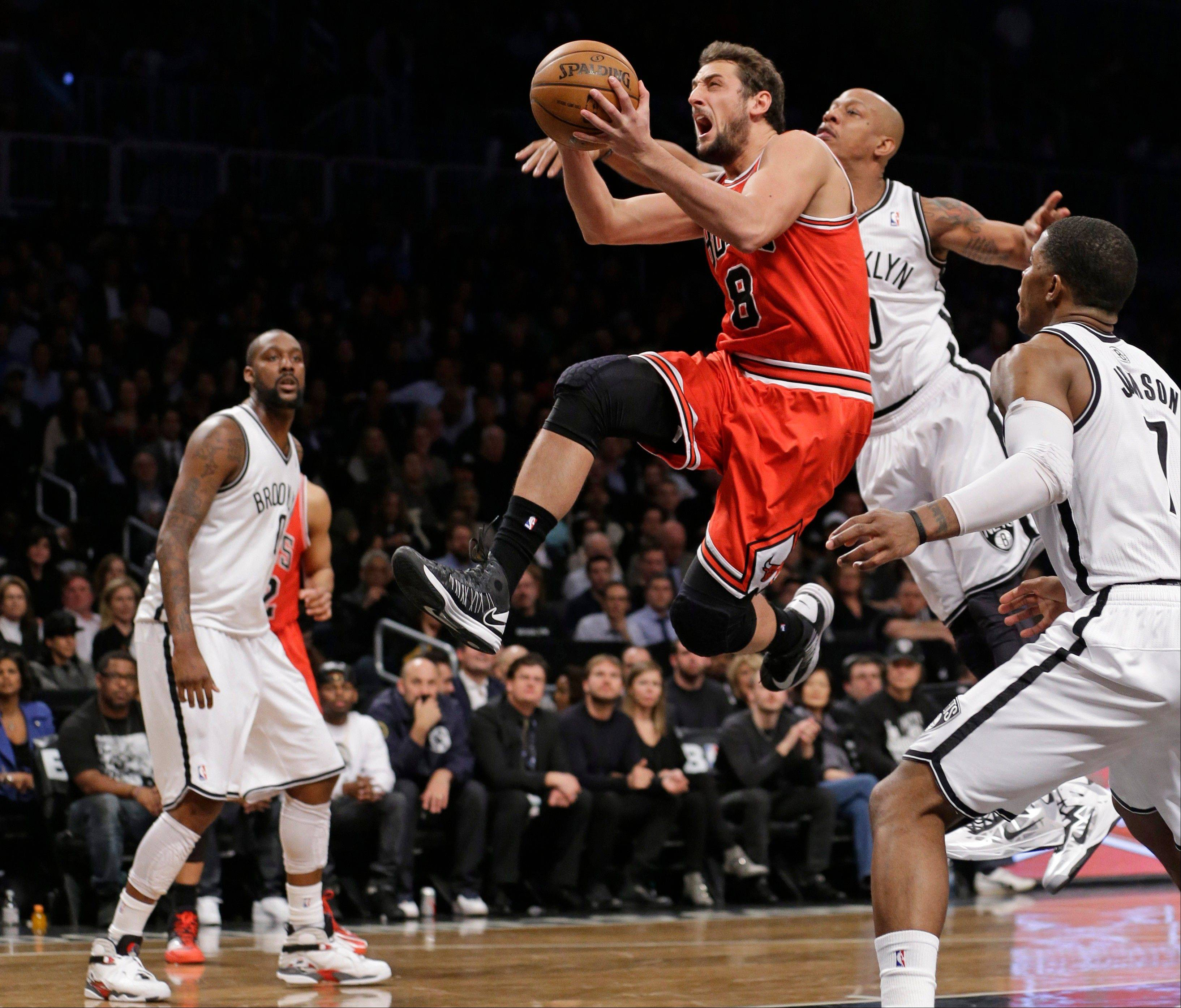Bulls guard Marco Belinelli (8) goes up for a layup past Brooklyn Nets forward Andray Blatche, left, forward Keith Bogans (10) and guard Joe Johnson (7) in the second half of Game 2 of their first-round NBA basketball playoff series, Monday, April 22, 2013, in New York. The Bulls won 90-82.