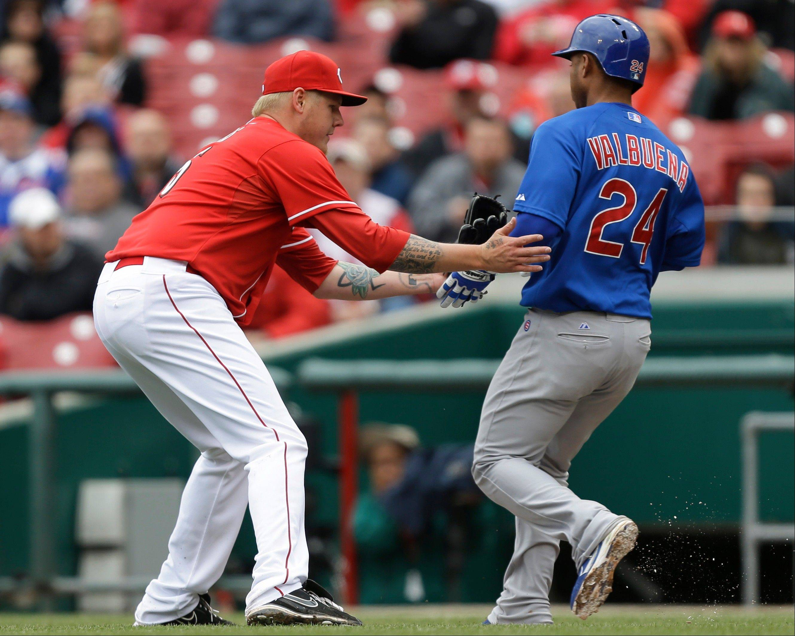 Cincinnati Reds starting pitcher Mat Latos tags out Chicago Cubs' Luis Valbuena (24) after Latos fielded a ground ball Wednesday in Cincinnati. The Cubs lost to the Reds 1-0.