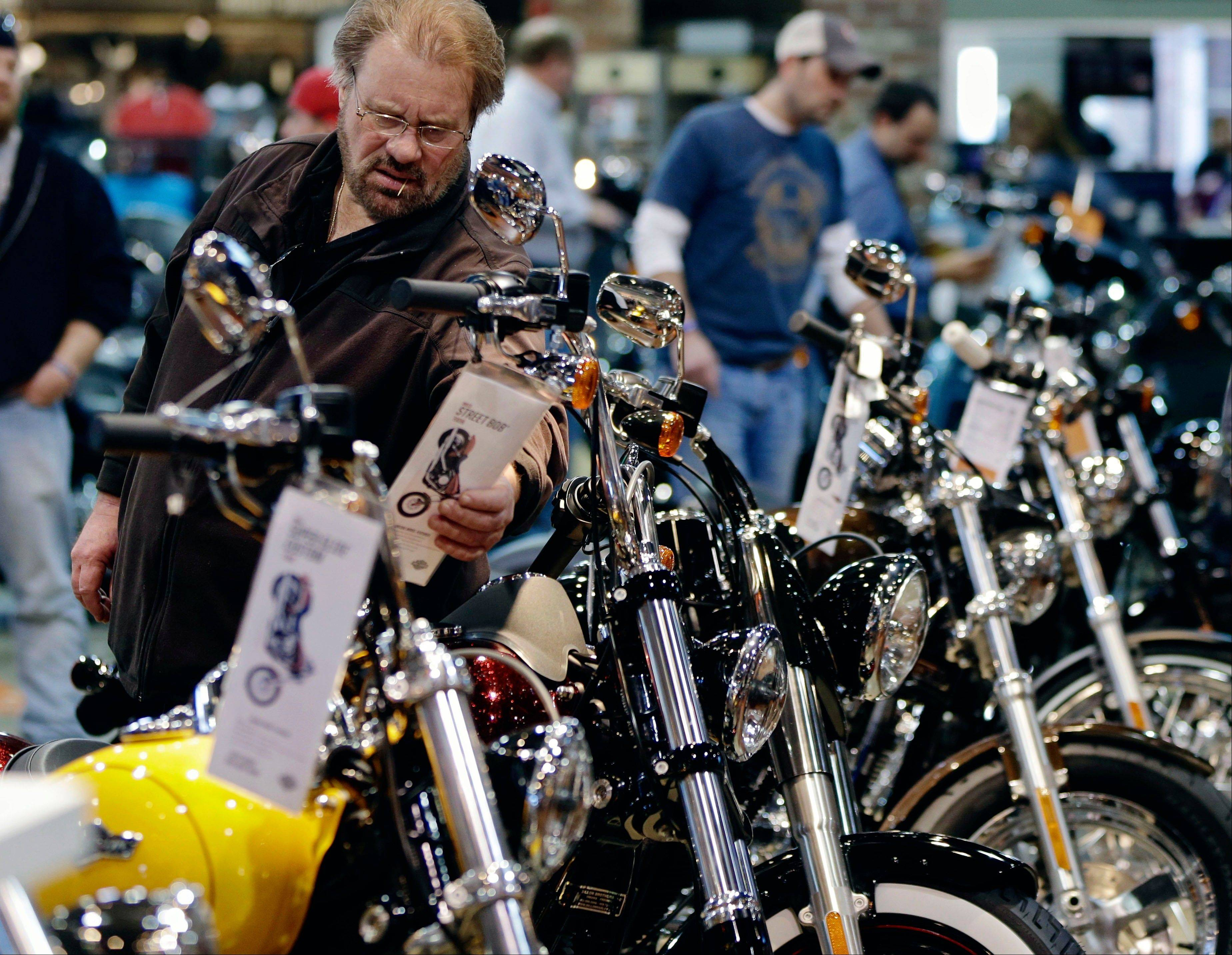 A man examines the tag of a motorcycle at the Dillon Brothers Harley Davidson dealership in Omaha, Neb. Harley-Davidson Inc. reported strong quarterly financial results before the market opened on Thursday.
