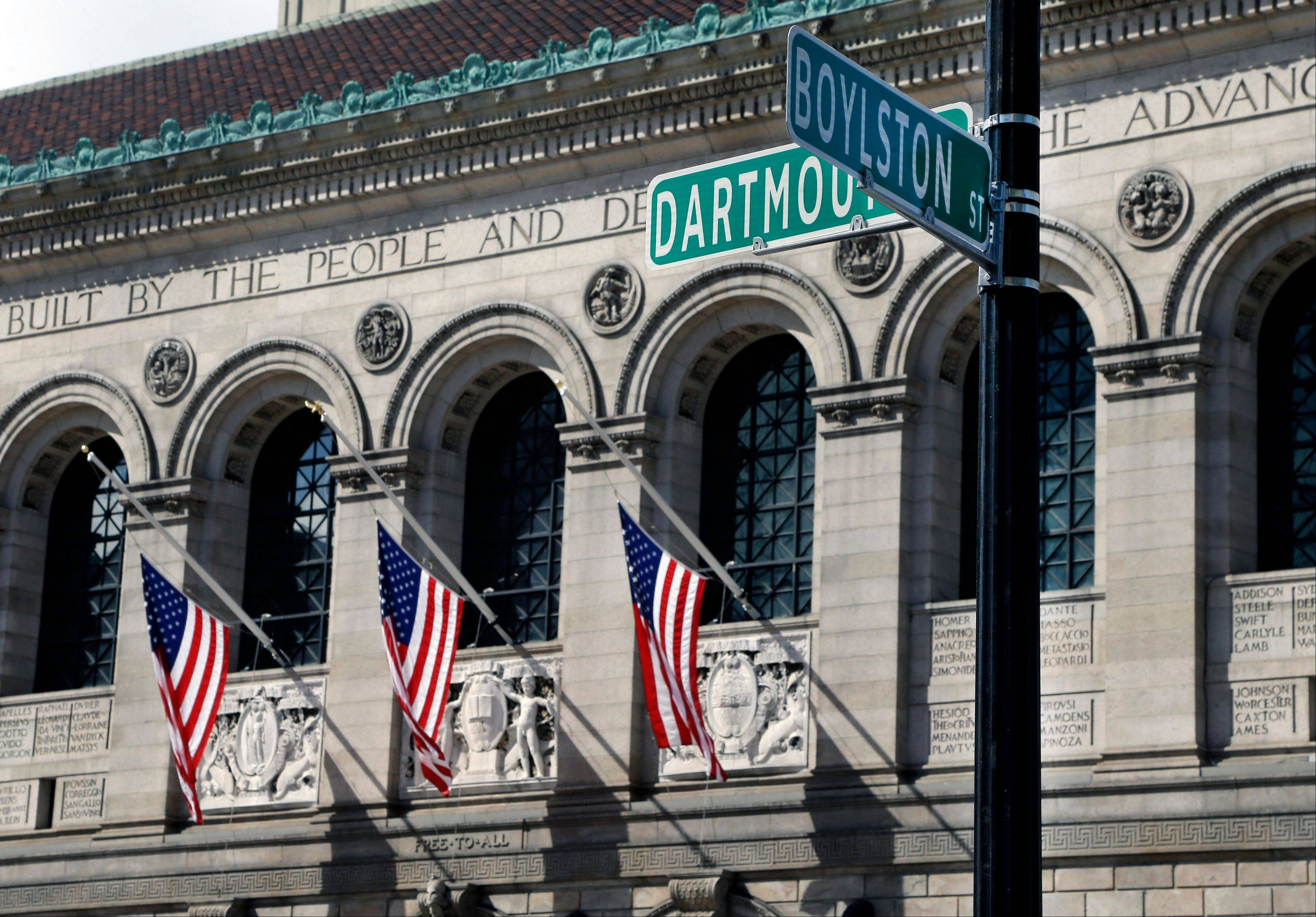 Flags on the Boston Public Library remain at half-staff Thursday near the Boston Marathon finish line.