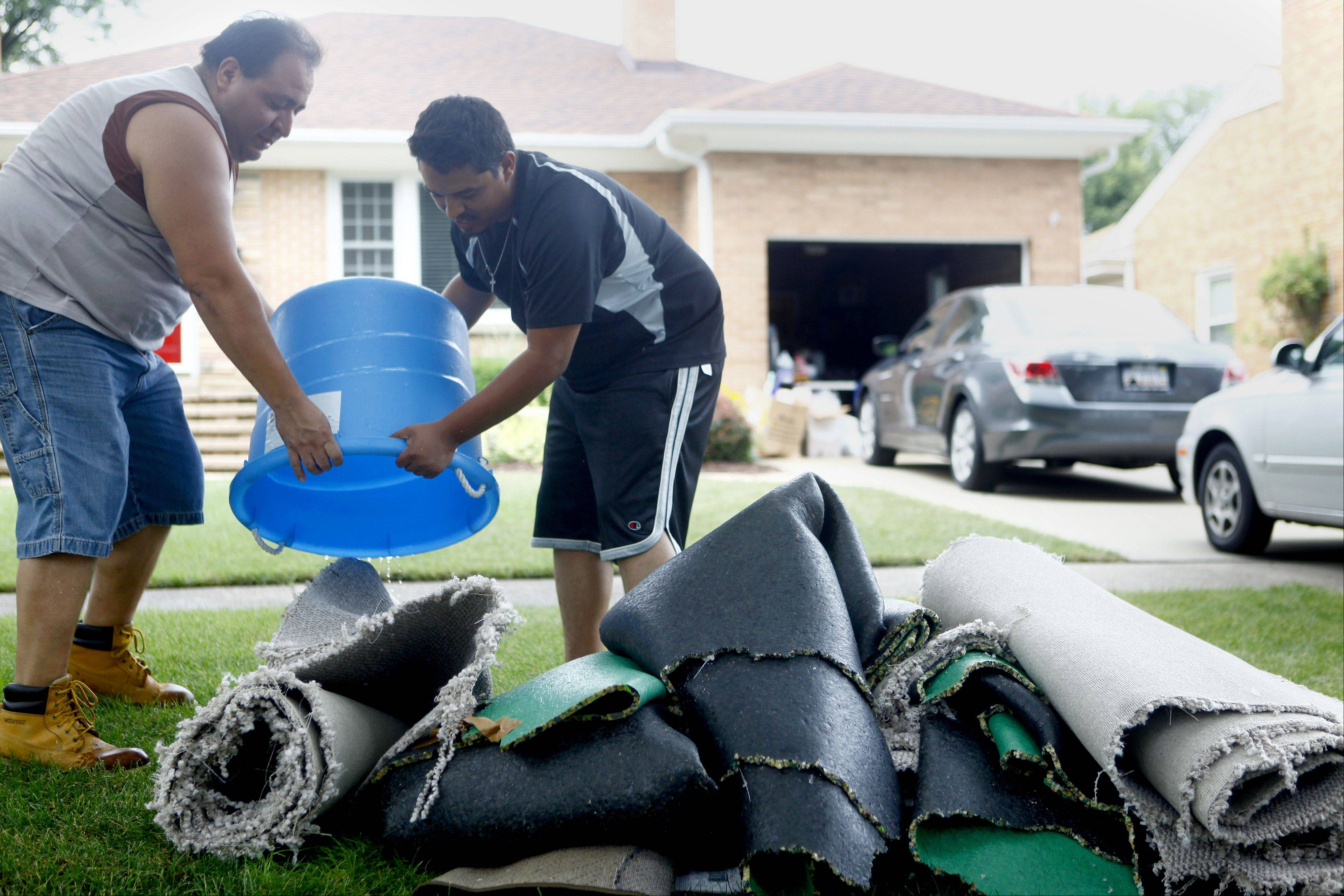 Mark Mesa, left, and Jorge Avina, carry out carpet from Mesa�s brother�s basement in Mount Prospect after heavy rains left six inches of water in the basement in 2011. Mount Prospect is considering a program to help homeowners prevent sewer backups.