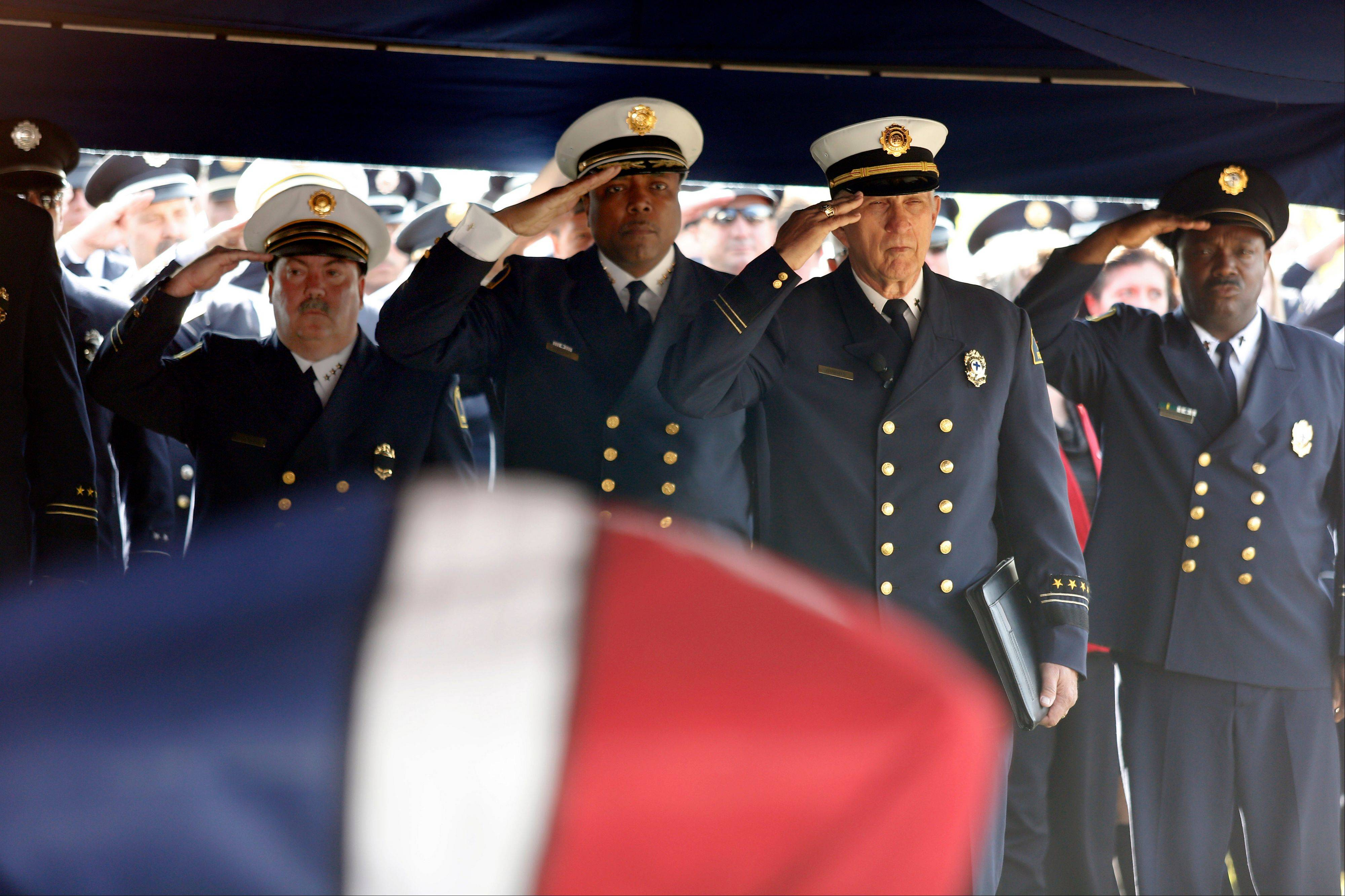 Dallas Fire-Rescue Chief Louie Bright, III, second left, and retired Dallas Fire Department Chaplain Denny Burris, second right, salute the casket of Dallas Fire-Rescue Captain Kenneth �Luckey� Harris, Jr. during his funeral at the Bold Springs Cemetery in West, Texas, on Wednesday April 24, 2013. Harris was killed in the West Fertilizer Co. plant explosion on April 17.