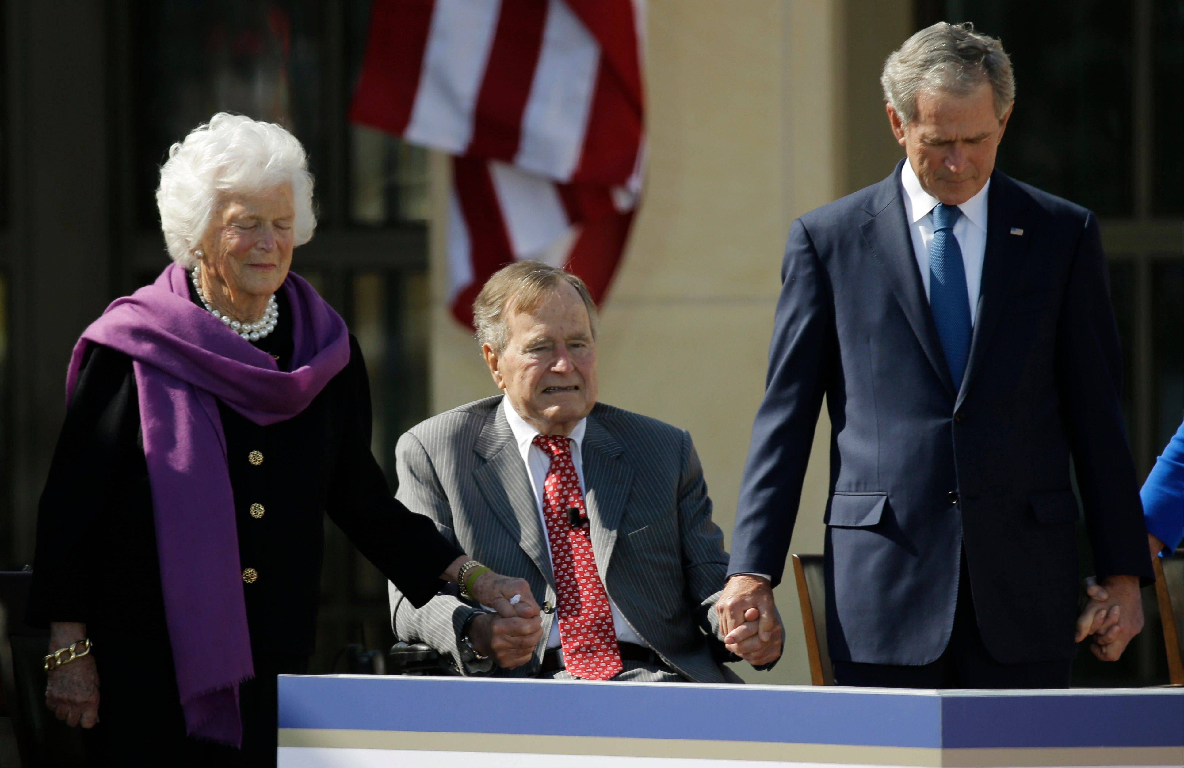 From left, former first lady Barbara Bush, President George H.W. Bush and former President George W. Bush hold hands during the invocation during the dedication of the George W. Bush Presidential Center Thursday, April 25, 2013, in Dallas.