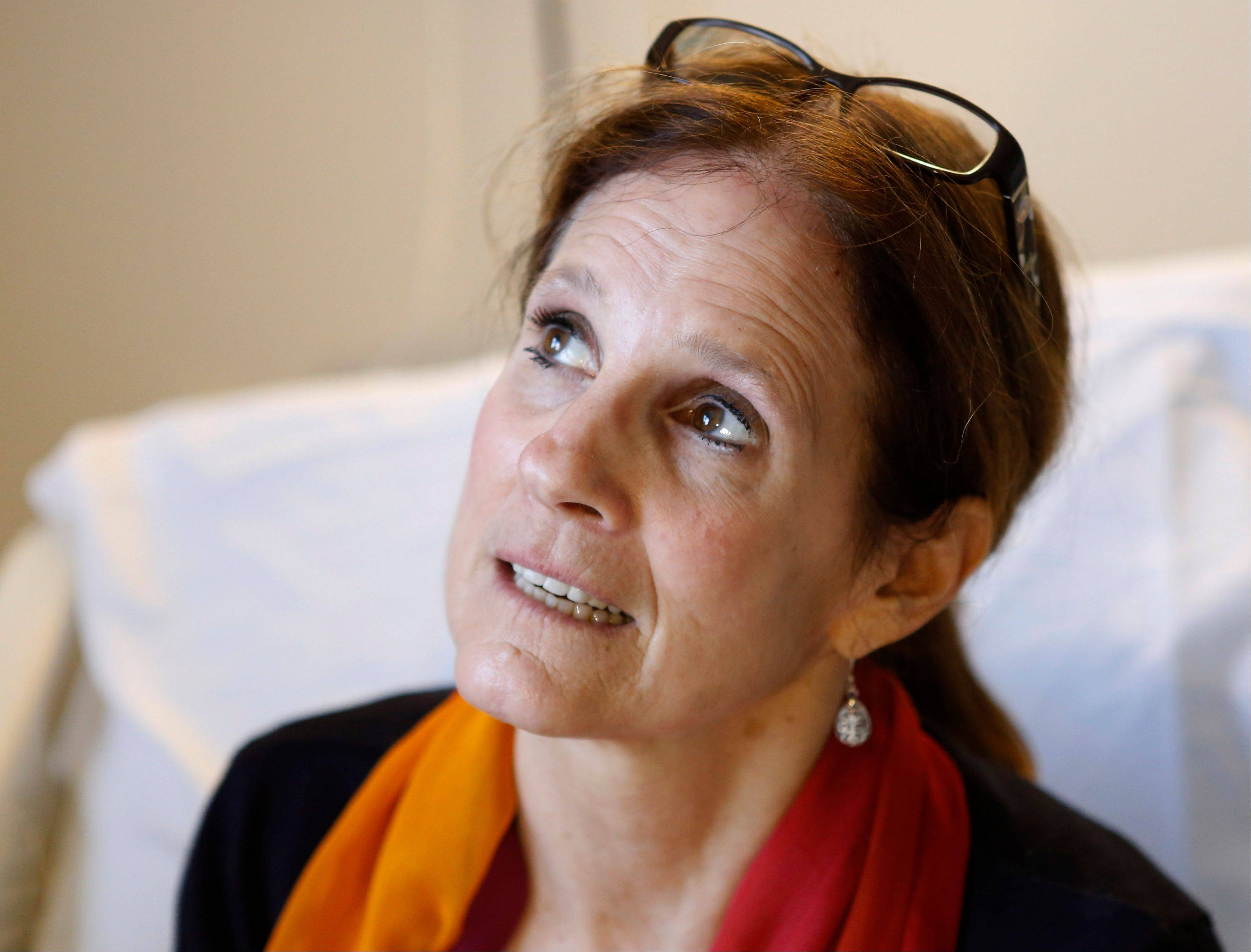 Beth Roche, whose left leg was severely injured by one of the bombs that exploded near the Boston Marathon finish line, sits on her bed at Spaulding Rehabilitation Hospital in Boston, Wednesday, April 24, 2013. The Indiana woman, who ran the Chicago Marathon last fall, was in Boston to watch her daughter Rebecca Roche run the Boston Marathon.