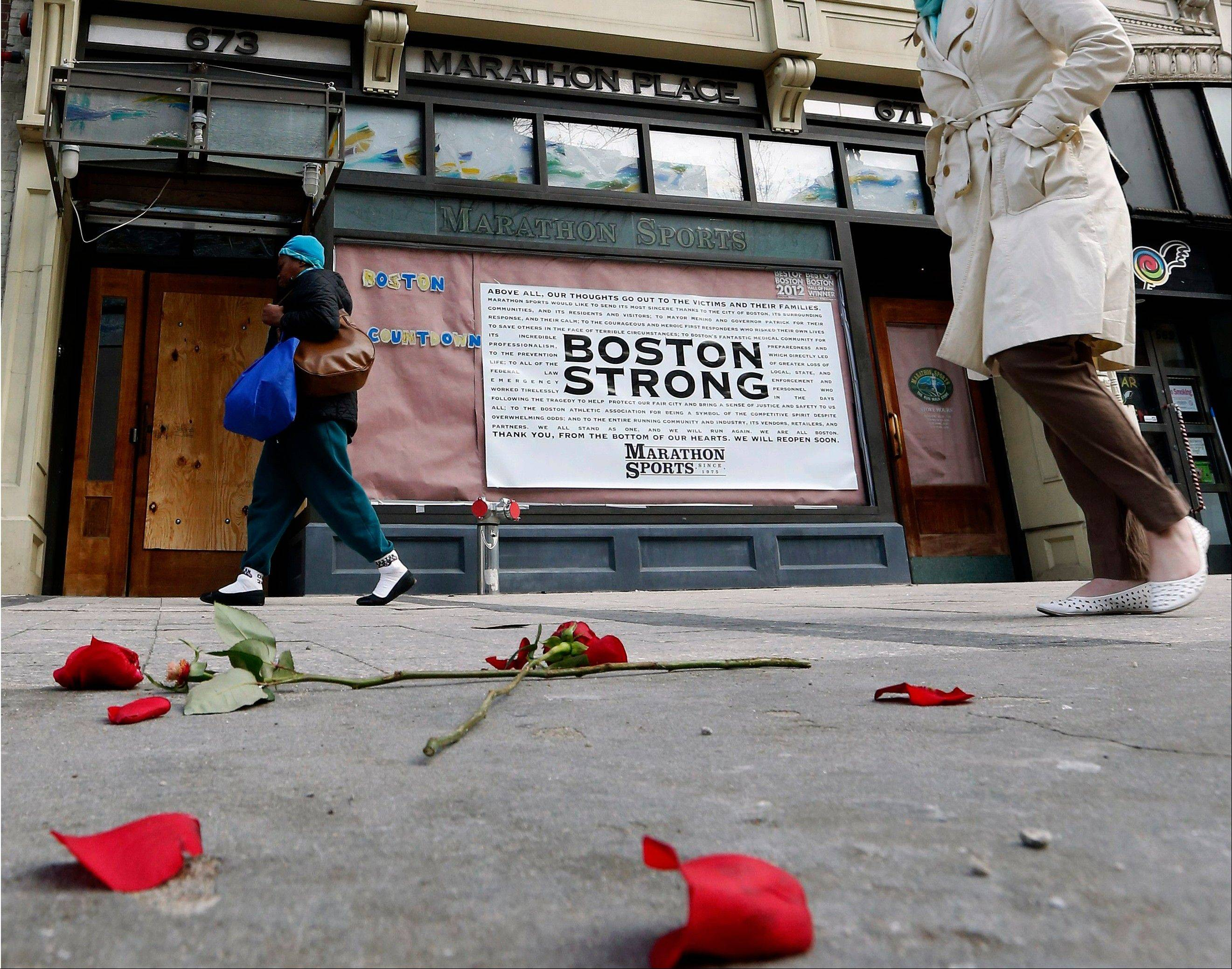 Pedestrians pass the spot where the first bomb detonated on Boylston Street near the finish line of the Boston Marathon Wednesday, April 24, 2013, in Boston. Traffic was allowed to flow all the way down Boylston Street on Wednesday morning for the first time since two explosions killed 3 people and injured many on April 15.