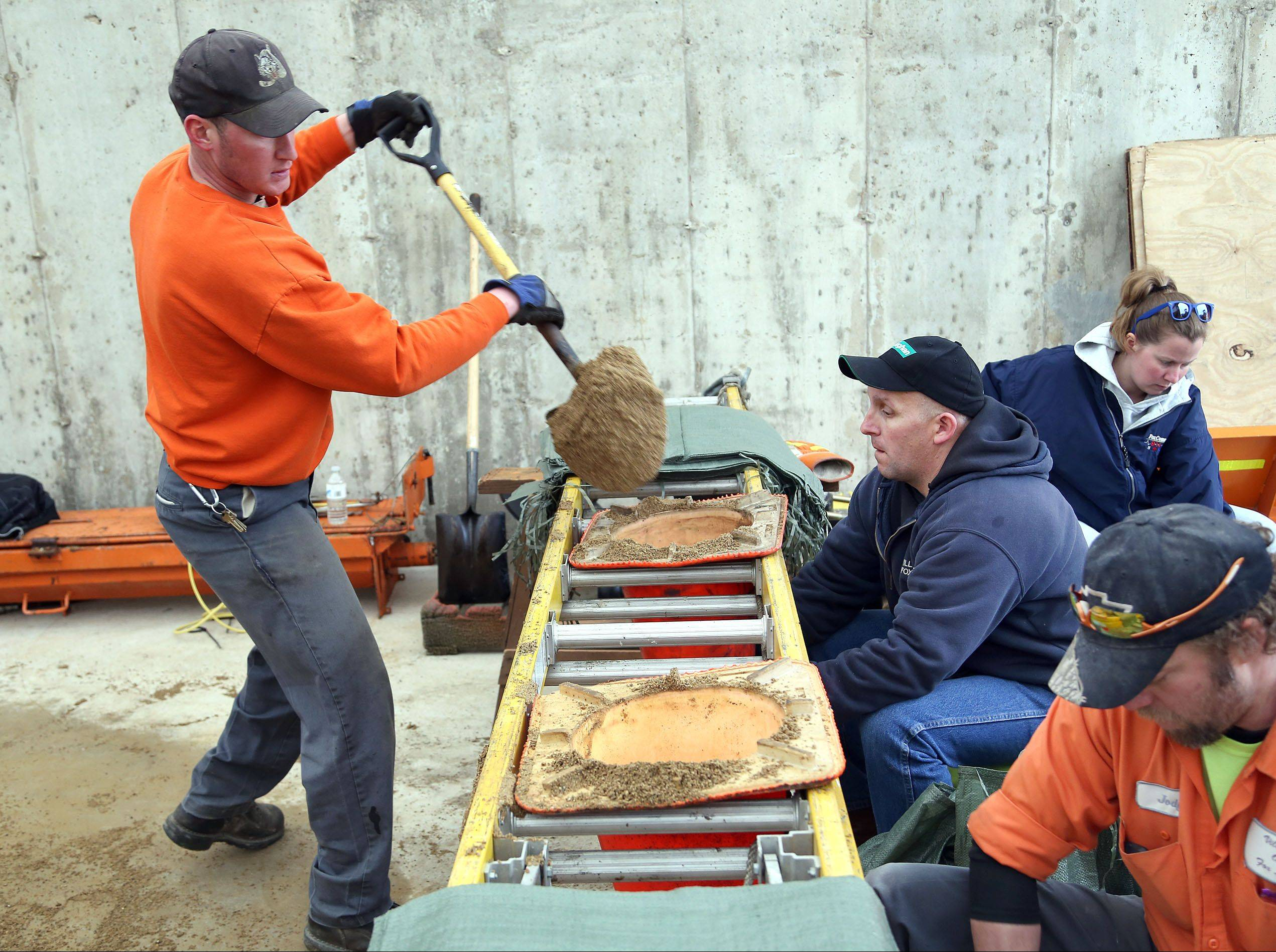 Dan Kattner, left, of the Fox Lake Street Department, and Matt Wood, of Fox Lake Water Treatment Plant, fill sandbags at the Fox Lake Public Works Department on April 12. Early reports suggest the cost to the county is more than $4.36 million, which would make it eligible for federal funds should a federal disaster declaration be made.
