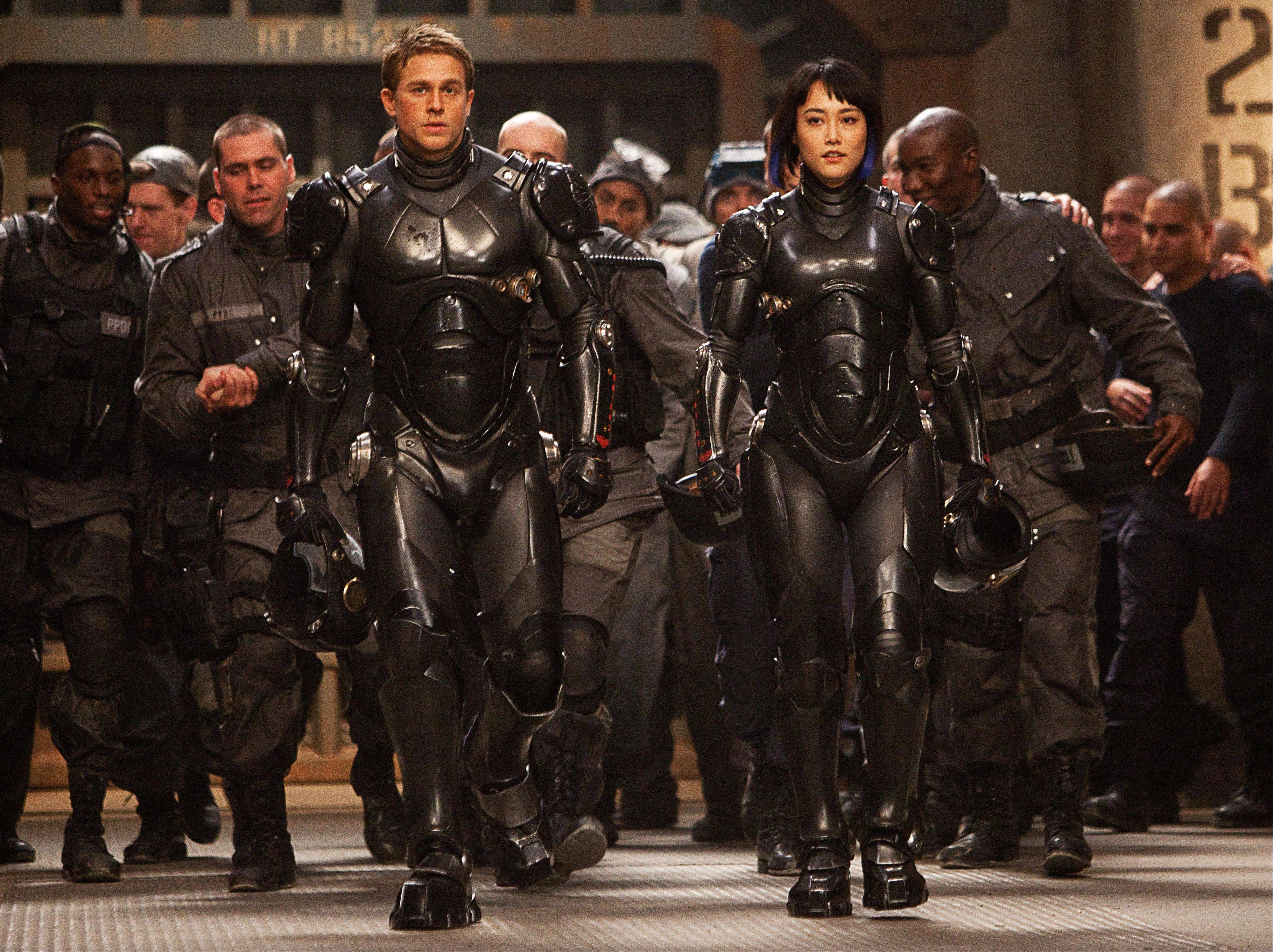 "Charlie Hunnam, front from left, stars as Raleigh Becket and Rinko Kikuchi as Mako Mori in the sci-fi action adventure ""�Pacific Rim."""