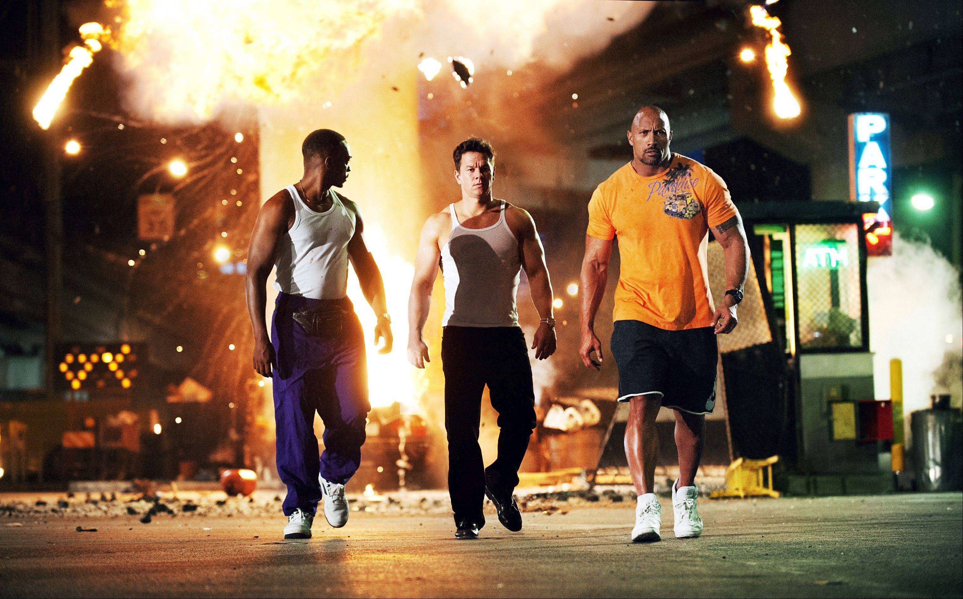 "Anthony Mackie, left, Mark Wahlberg and Dwayne Johnson perform an action-movie cliché as three bodybuilders trying to steal the American dream in Michael Bay's ""Pain & Gain."""