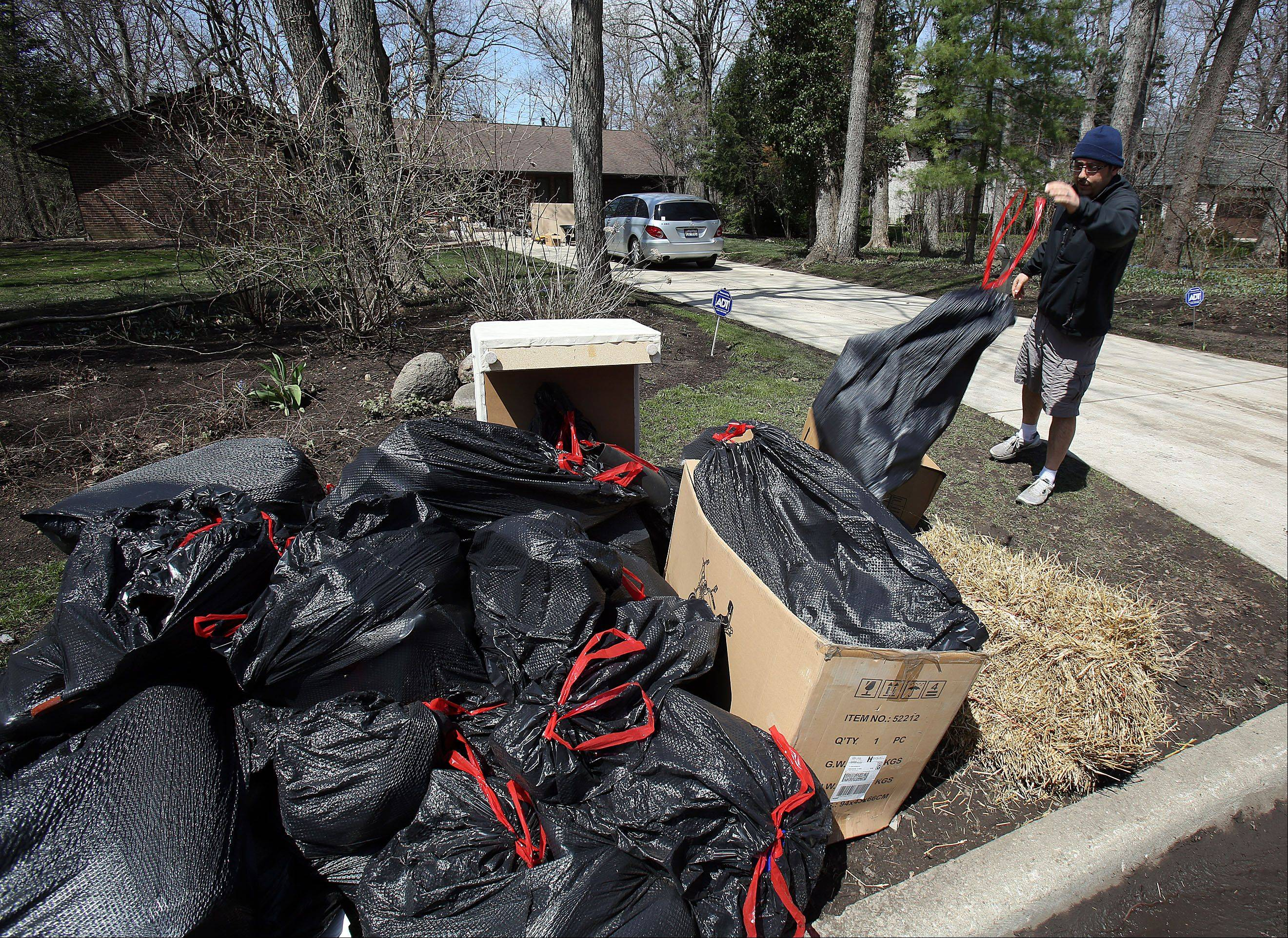 "Karnig Kerkonian throws out flood damaged items from his house on Lincolnshire Drive Friday. ""The village told us we should have flood damaged items out to the street by 7 a.m. Saturday,"" Kerkonian said."