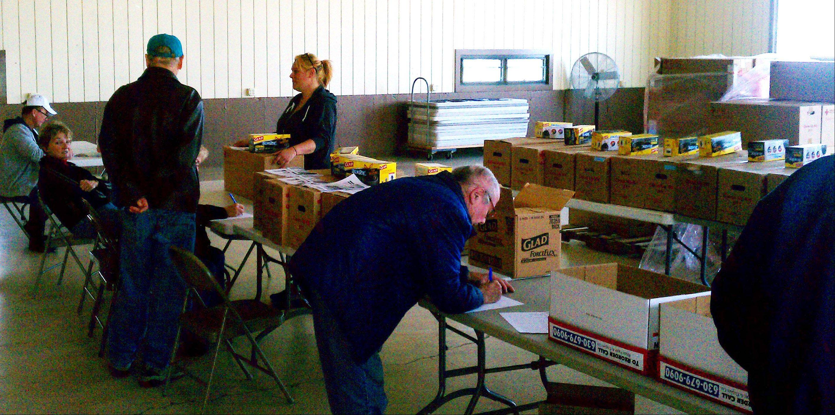 Residents fill out paperwork to receive free flood kits Friday morning at Lakefront Park in Fox Lake.
