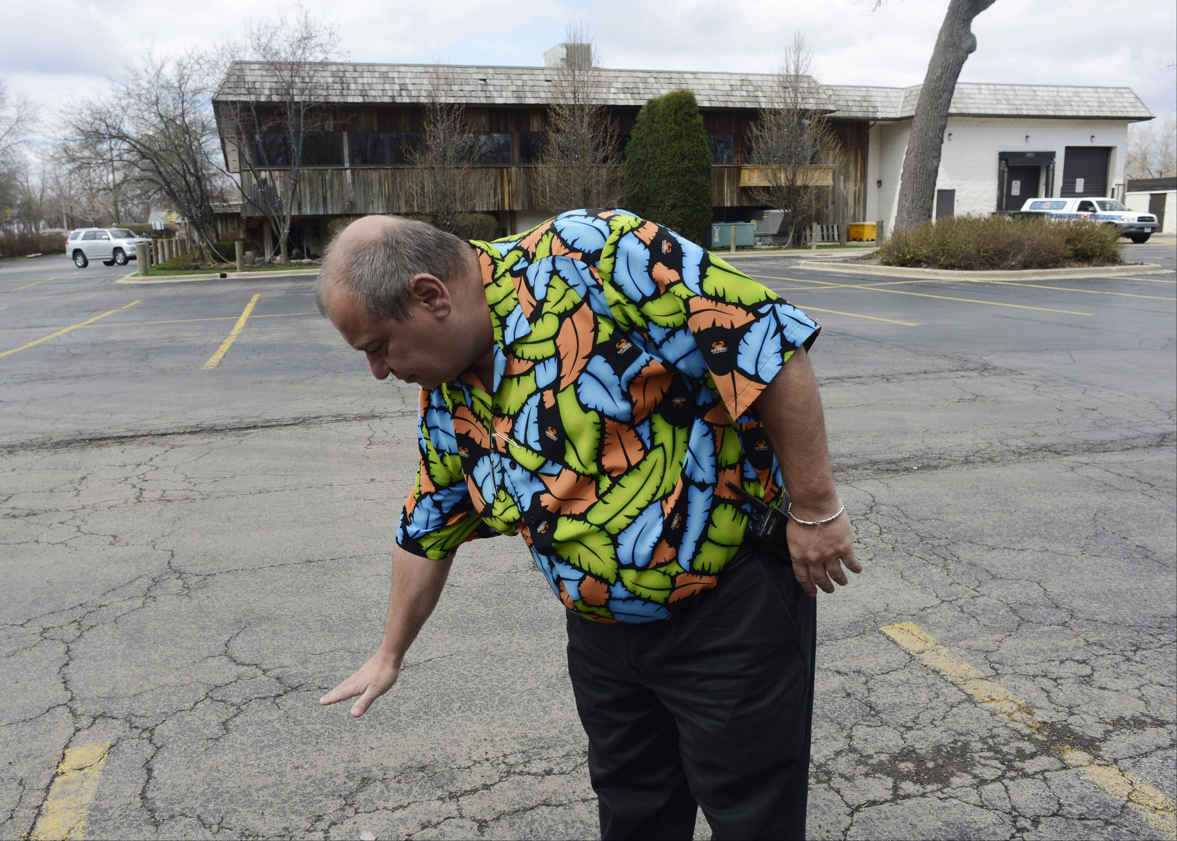 Deno Roumanidakis, director of operations at Bob Chinn's Crab House in Wheeling, shows the area of the parking lot that flooded when torrential rains last week drove the Des Plaines River over its banks. The restaurant was forced to close last weekend.