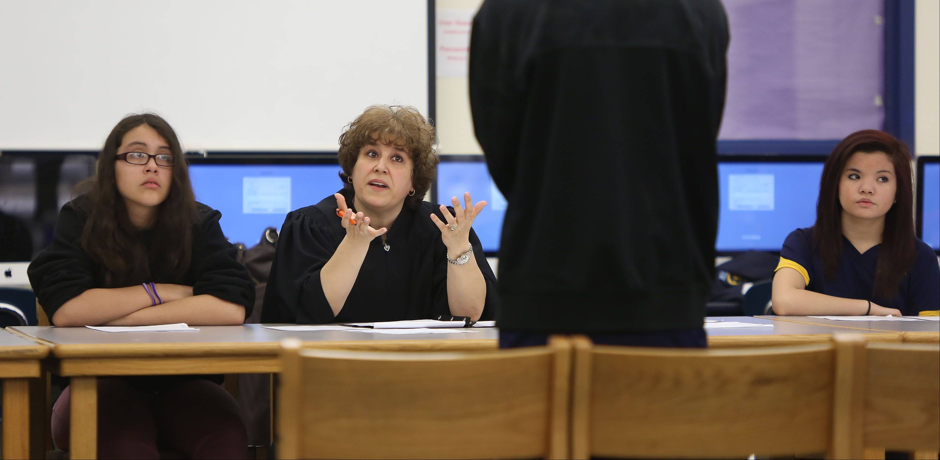 Attorney Lori Berdenis, of Round Lake Beach, acts as judge as jurors Ruby Guevara, left, and Makena Ridiros listen during Peer Court at Round Lake Middle School. The program is an alternative to suspension or other disciplinary measures for students who qualify.