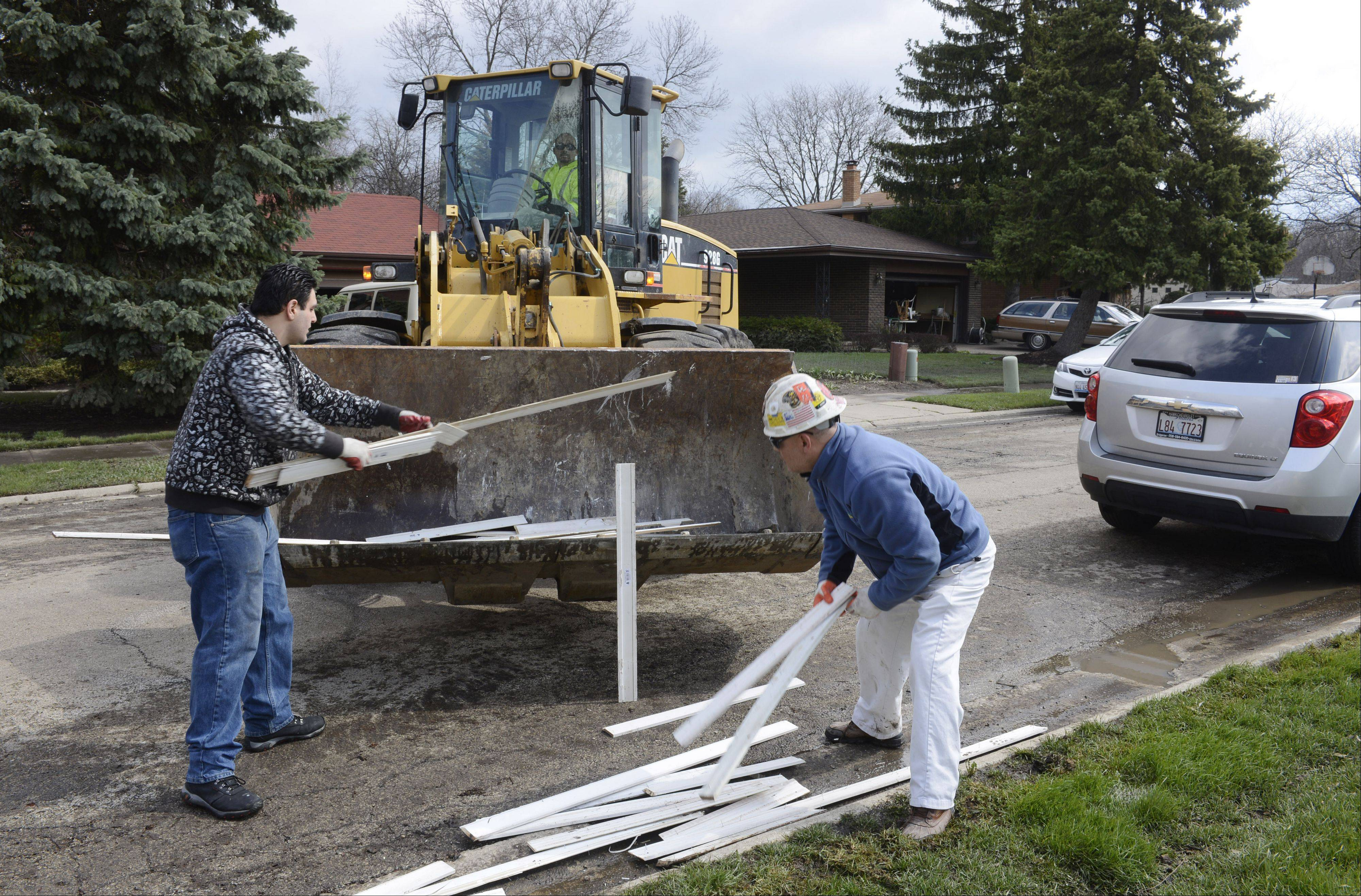 Viorel Domasneanu, left, and Francisco Michel of ServiceMaster Restoration load damaged trim onto a front loader on Big Bend Road in Des Plaines while assisting with damage from last week's Des Plaines River flooding.
