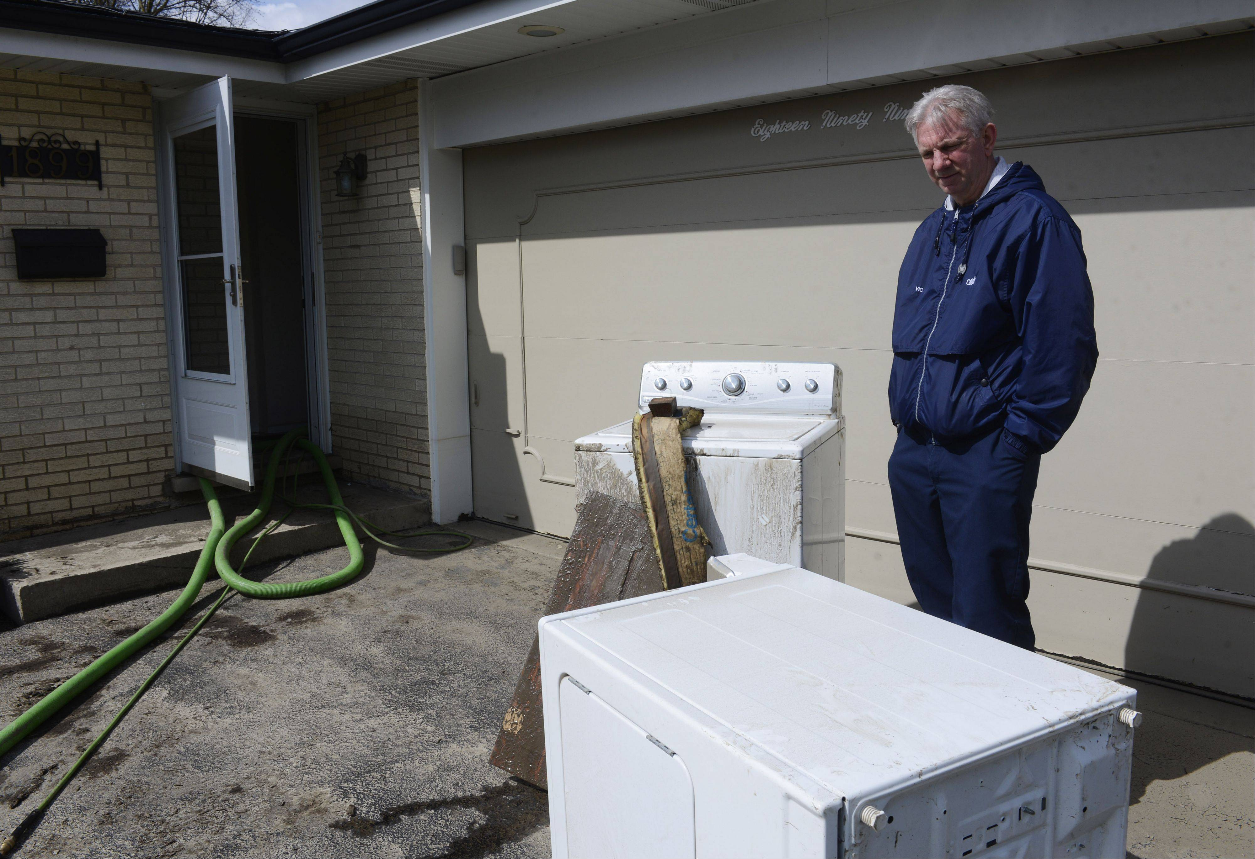 Vic Kamka, who lives on Big Bend Road in Des Plaines, stands beside a washer and dryer that were purchased new in 2008, only to be destroyed in last week's Des Plaines River flood.