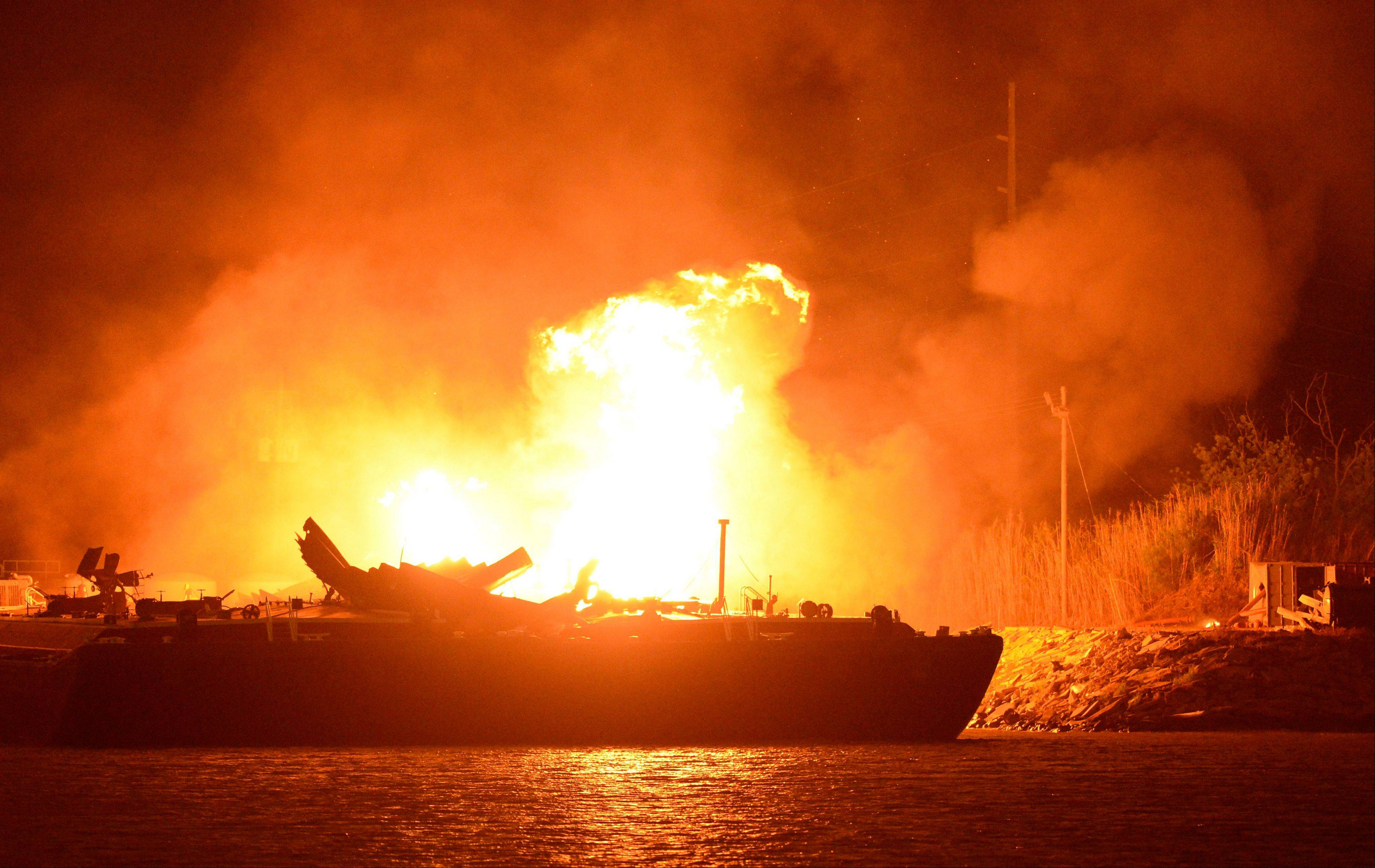 A massive explosion at 3 a.m. EDT on one of the two barges still ablaze in the Mobile River in Mobile, Ala., on Thursday, April 25, 2013. Three people were injured in the blast. Fire officials have pulled units back from fighting the fire due to the explosions and no immediate threat to lives.