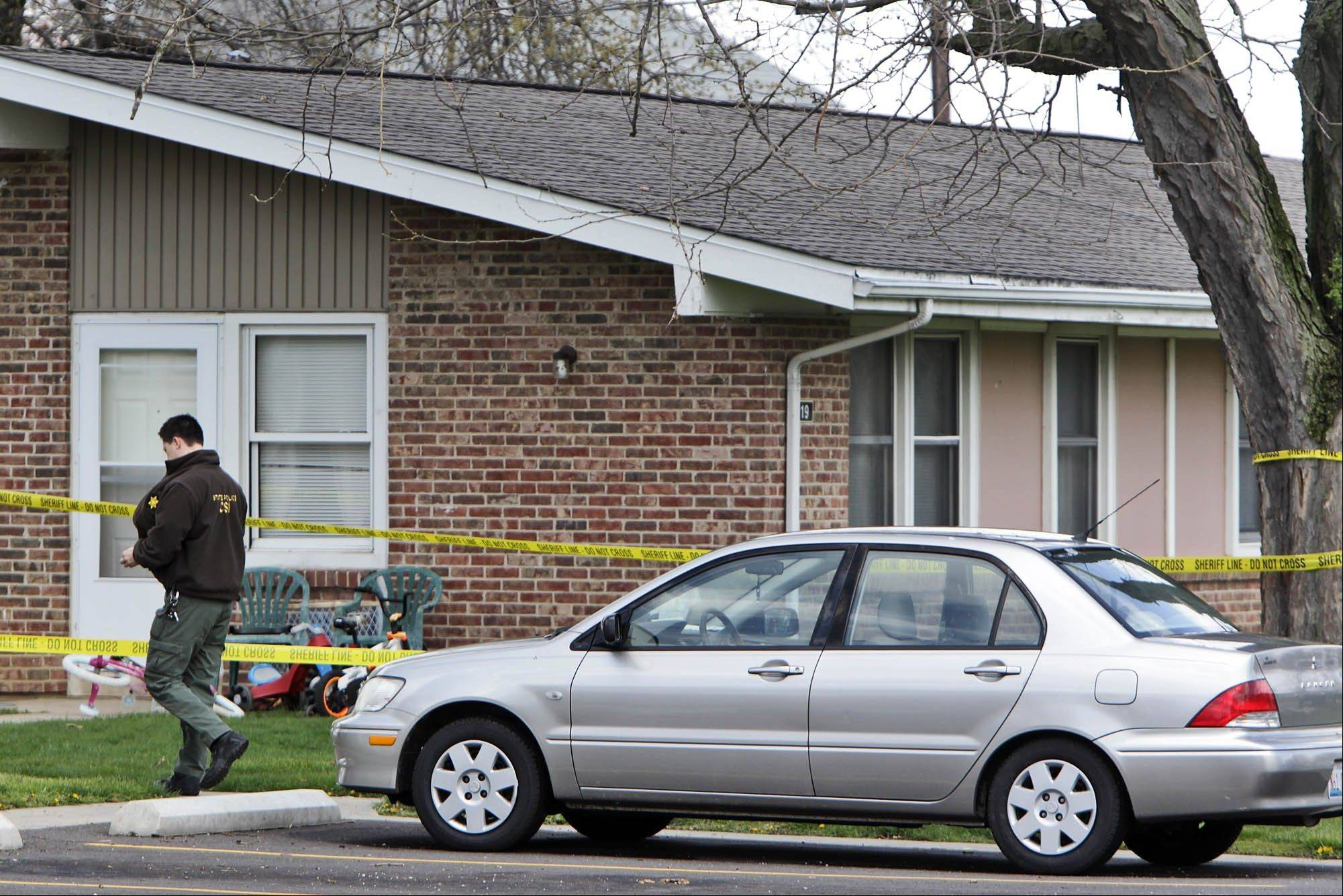 An Illinois State Police investigator walks past the housing complex where 5 people were killed Wednesday.