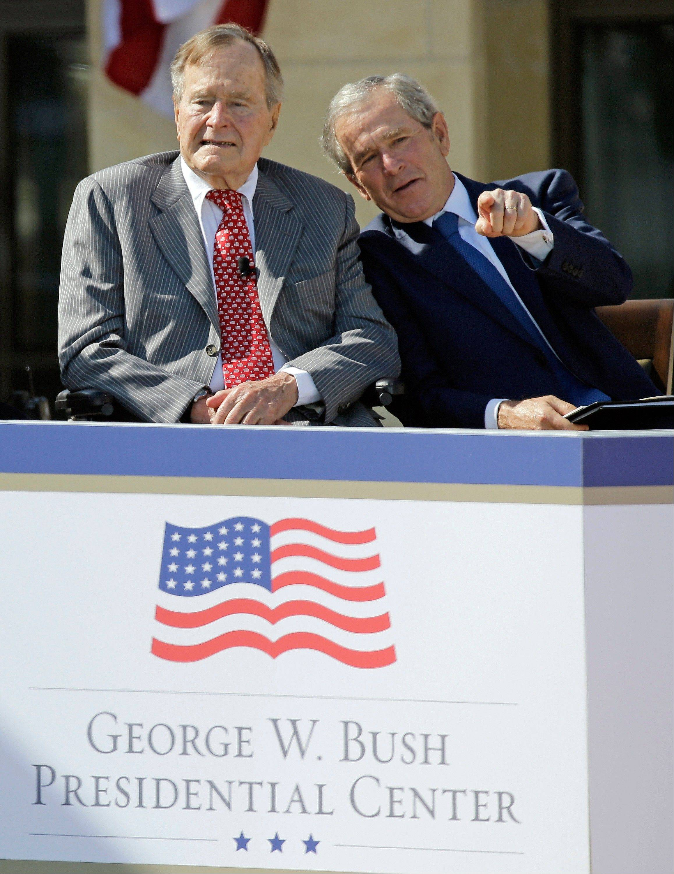 Former President George W. Bush talks with his father, former President George H.W. Bush, left, during the dedication of the George W. Bush Presidential Center, Thursday, April 25, 2013, in Dallas.