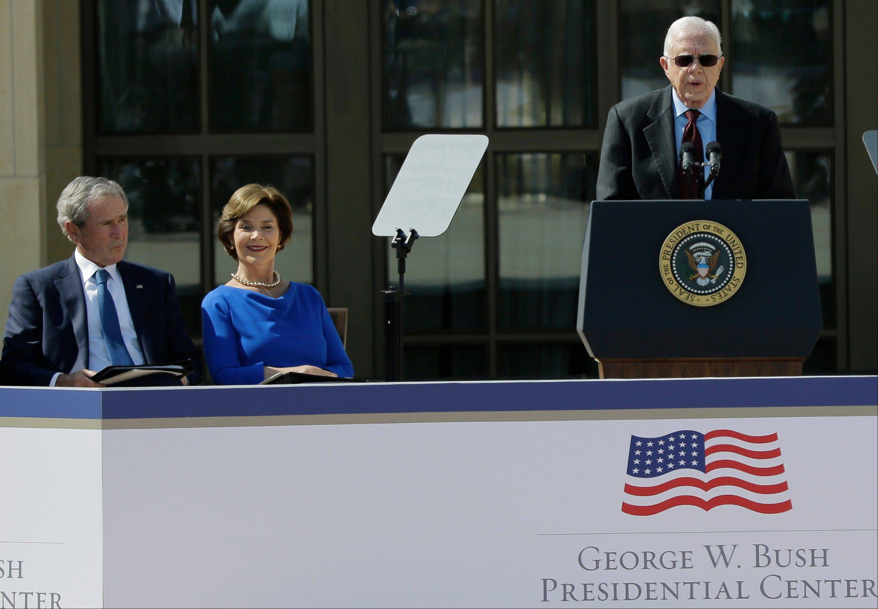 Former President George W. Bush and his wife Laura Bush listen to former president Jimmy Carter during the dedication of the George W. Bush Presidential Center Thursday, April 25, 2013, in Dallas.