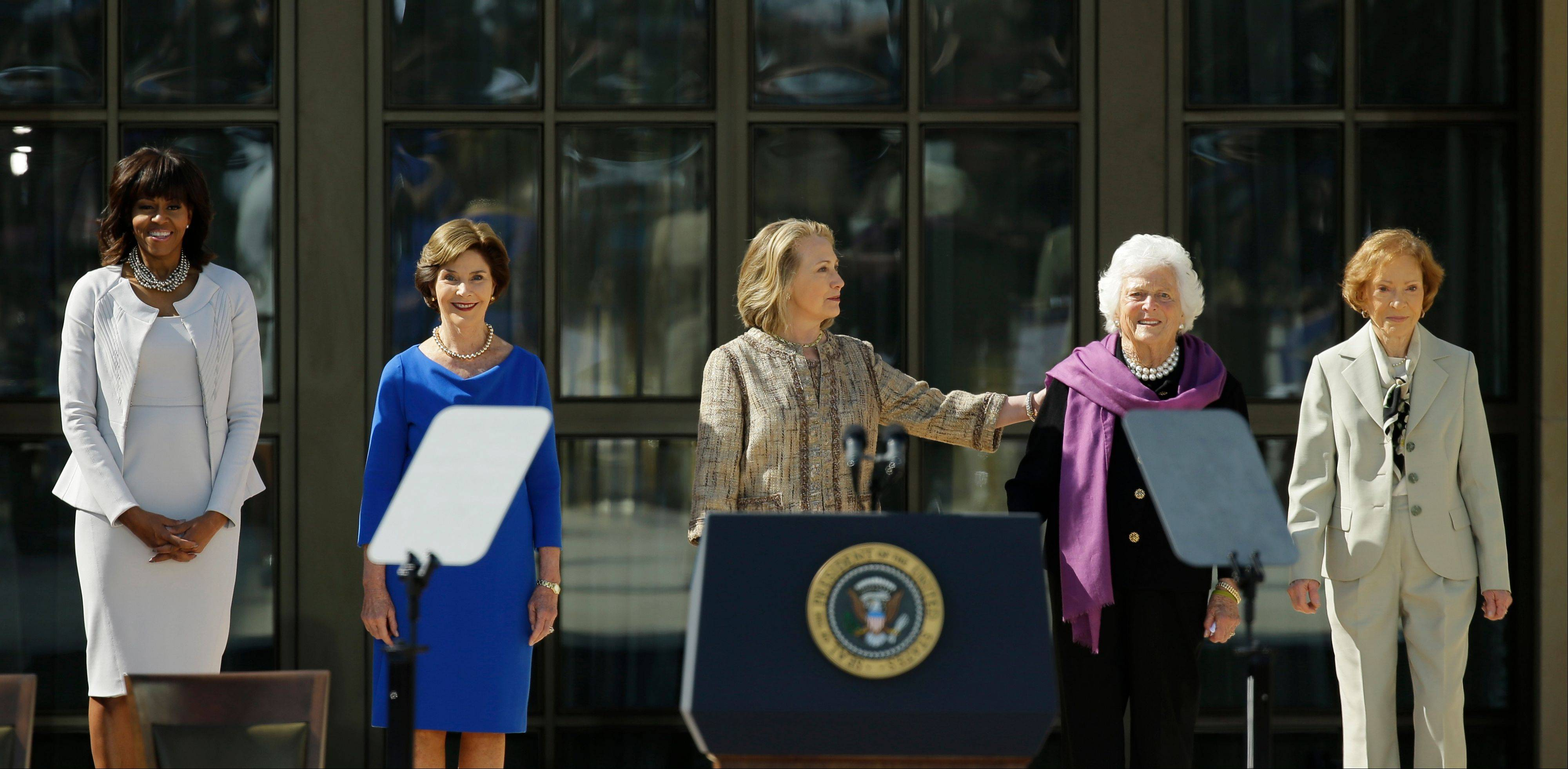 From left, first lady Michelle Obama, former first lady Laura Bush, former first lady Hillary Clinton, former first lady Barbara Bush and former first lady Rosalynn Carter arrive for the dedication of the George W. Bush Presidential Center Thursday, April 25, 2013, in Dallas.