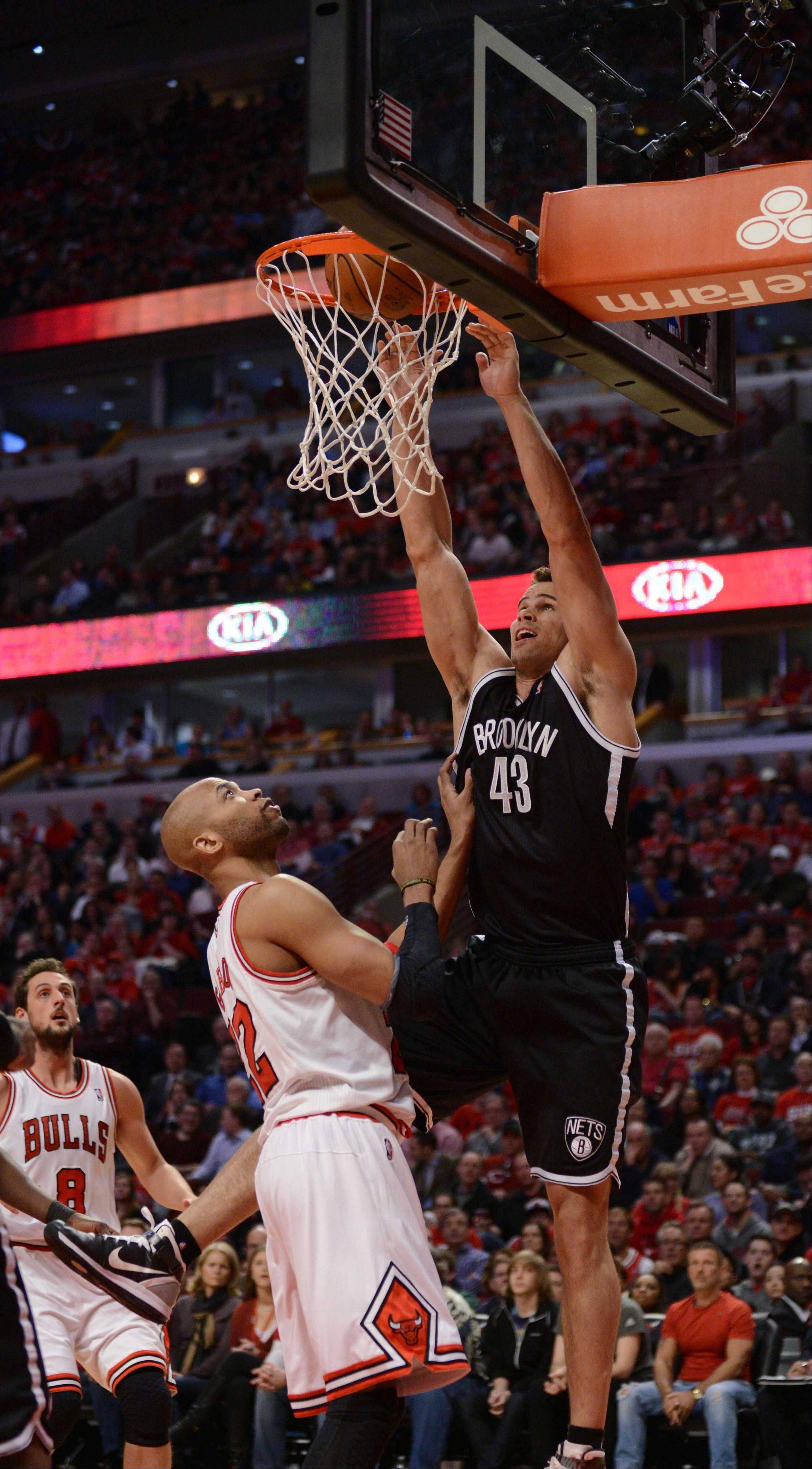 Kris Humphries of Brooklyn slams one as Taj Gibson of Chicago watches.