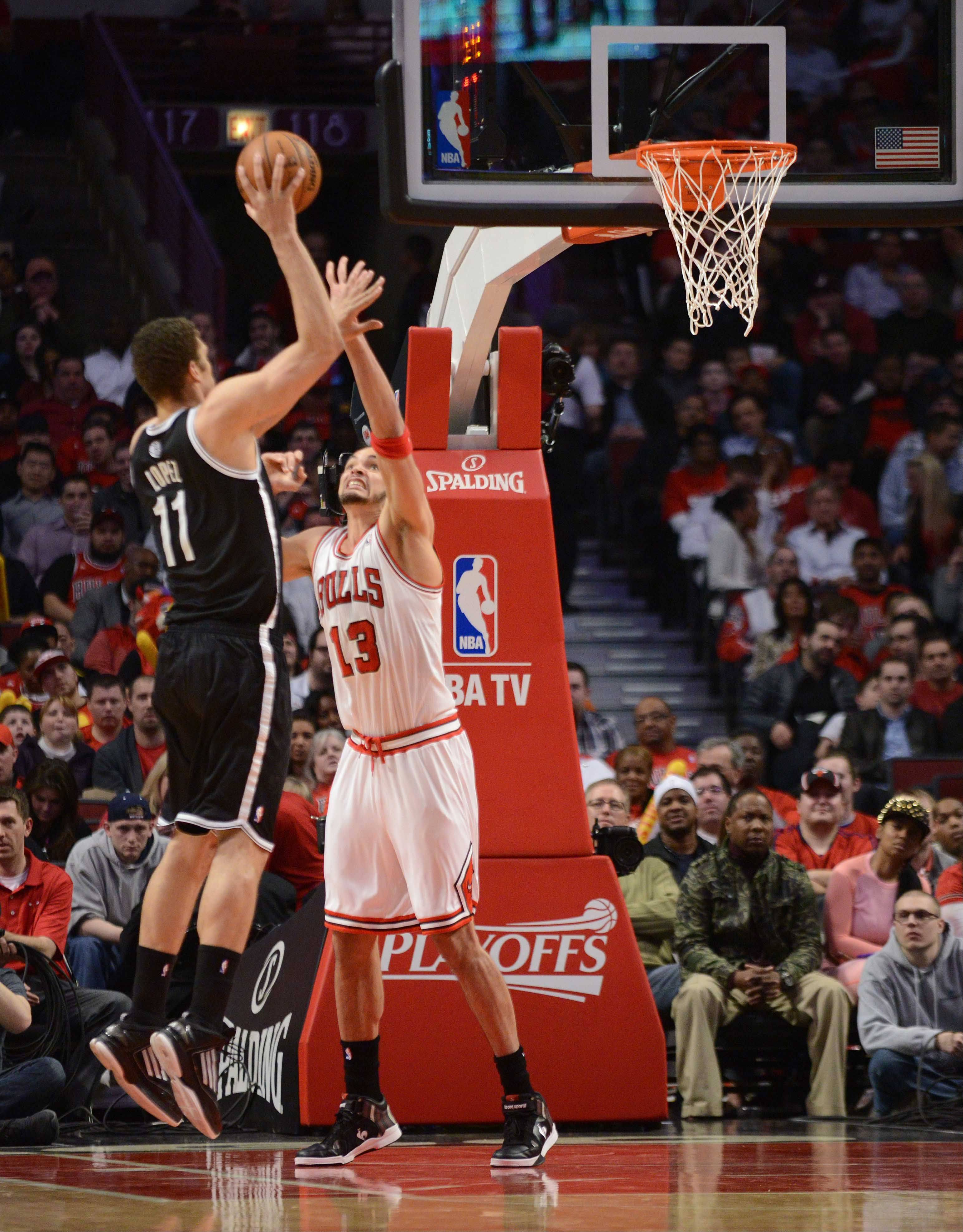 Brook Lopez of the Brooklyn Nets puts up a shot while Joakim Noah of Chicago tries to block.