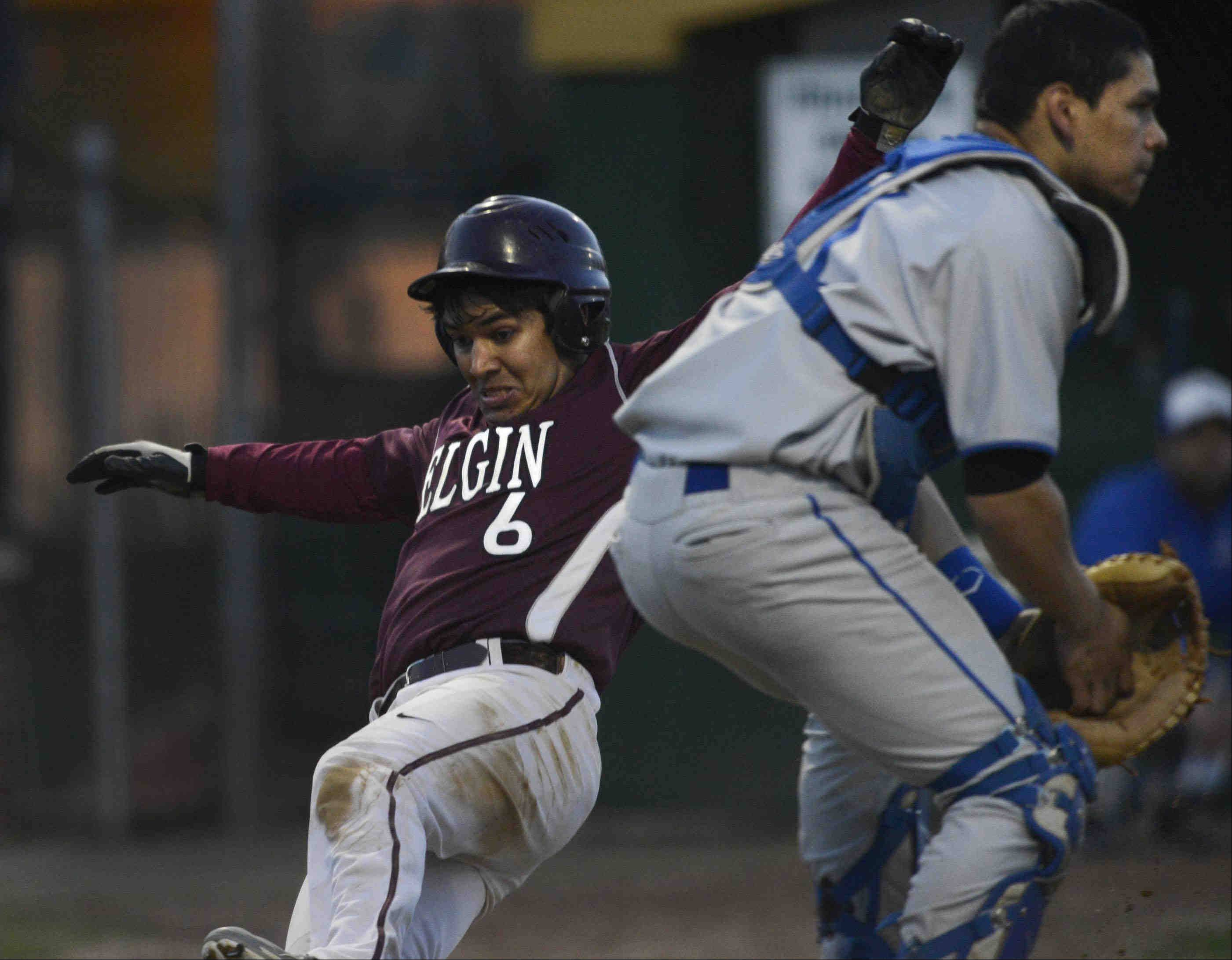 Elgin's Isaac Narayan scores during a rally in the sixth inning as Larkin catcher Niko Morado waits for the throw Thursday at Trout Park in Elgin.