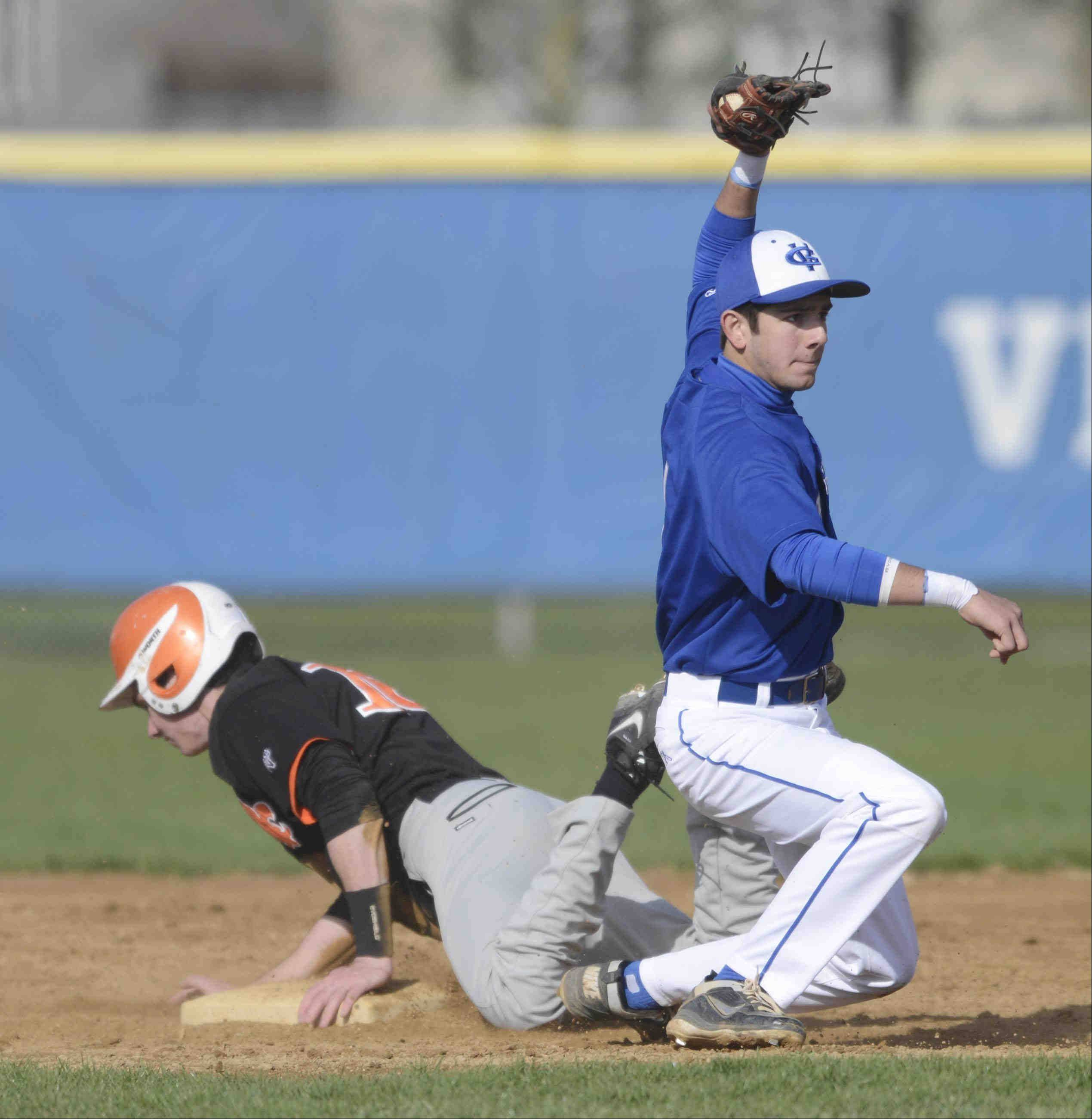 Geneva's Luke Polishak shows the umpire the ball after tagging out St. Charles East's Sean Dunne Thursday in Geneva.