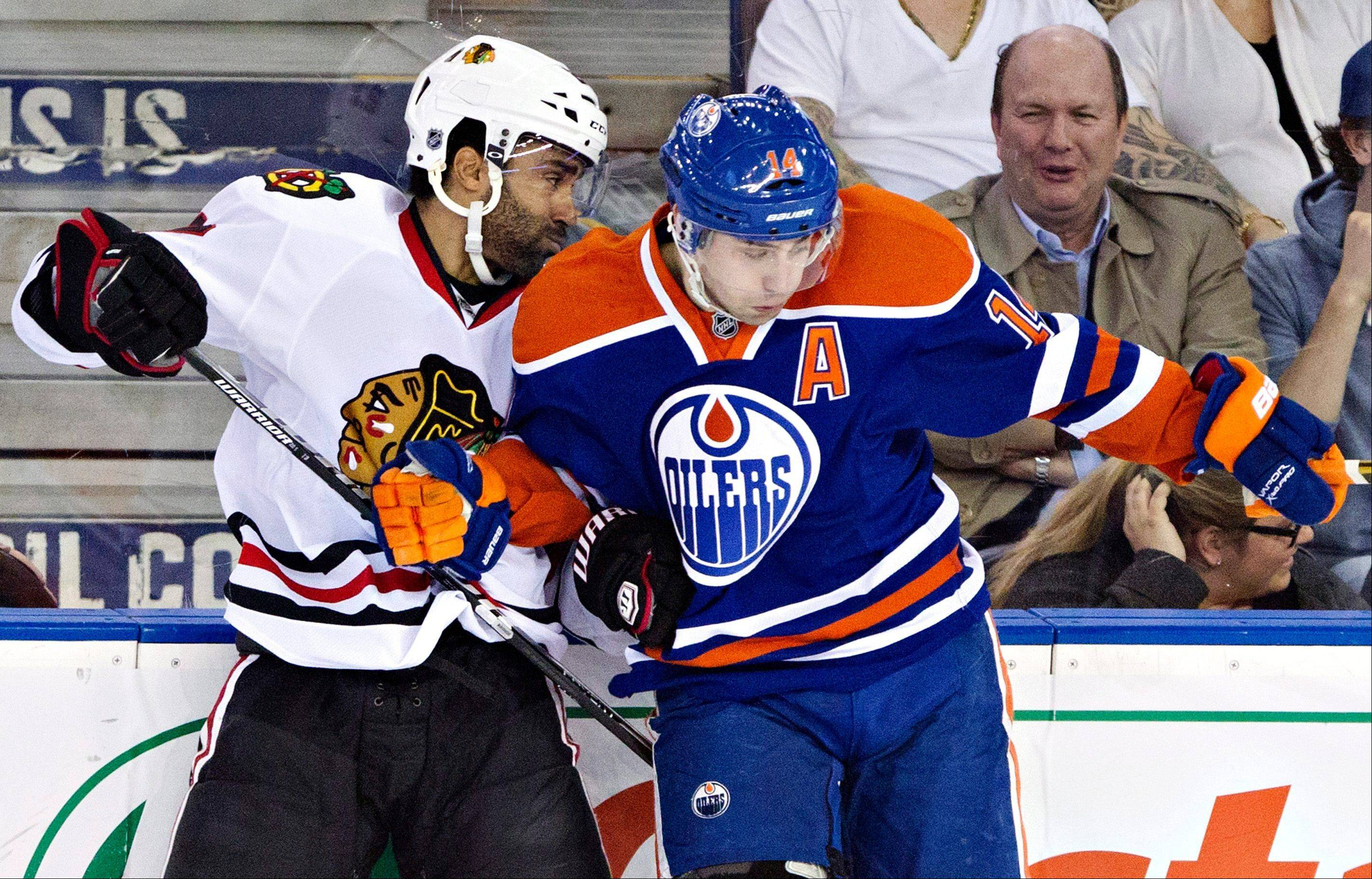 Chicago Blackhawks' Johnny Oduya, left, checks Edmonton Oilers' Jordan Eberle during the first period of their NHL hockey game in Edmonton, Alberta, Wednesday, April 24, 2013.
