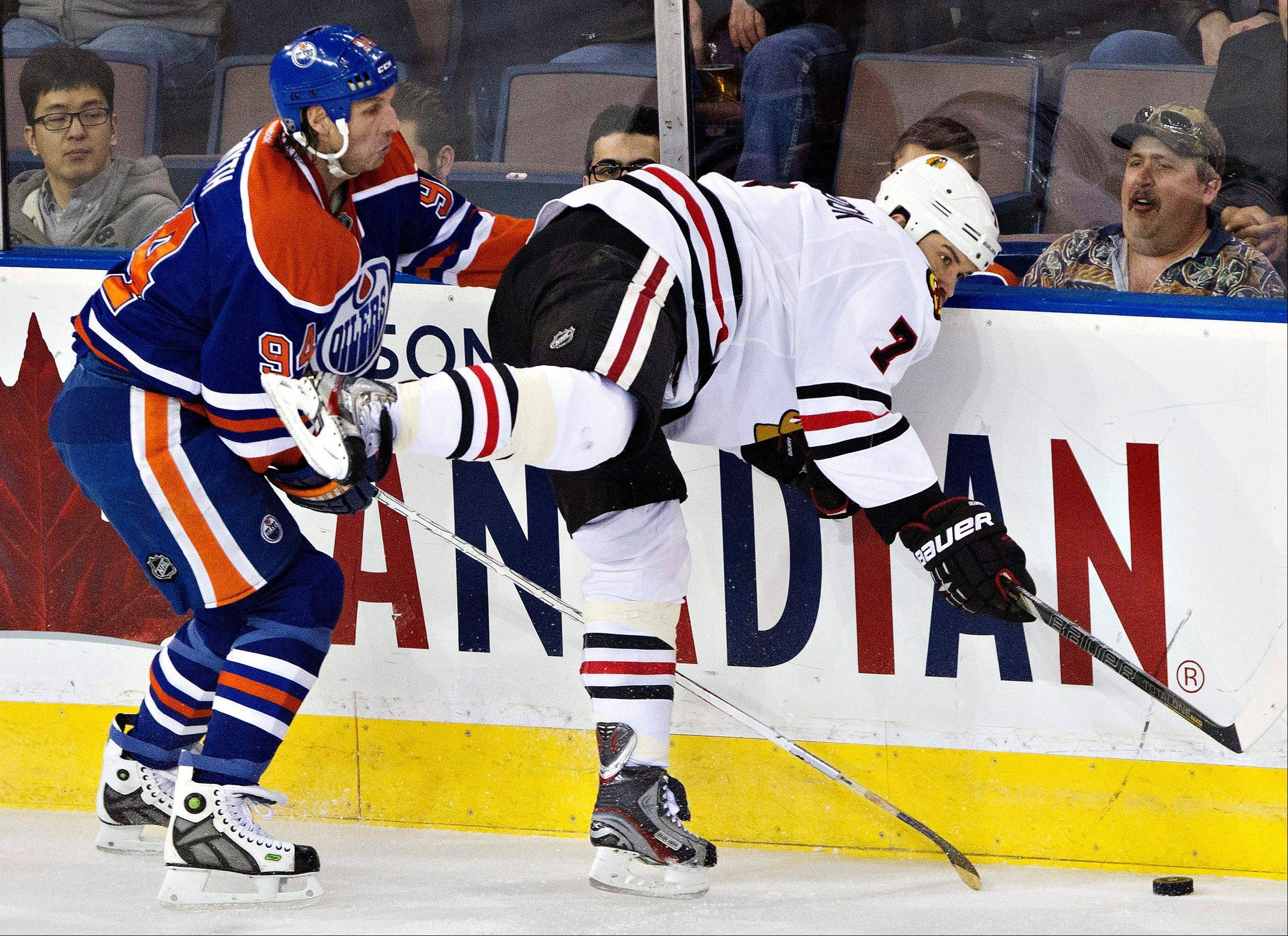 Chicago Blackhawks' Brent Seabrook (7) is checked by Edmonton Oilers' Ryan Smyth during the second period of their NHL hockey game in Edmonton, Alberta, Wednesday, April 24, 2013.