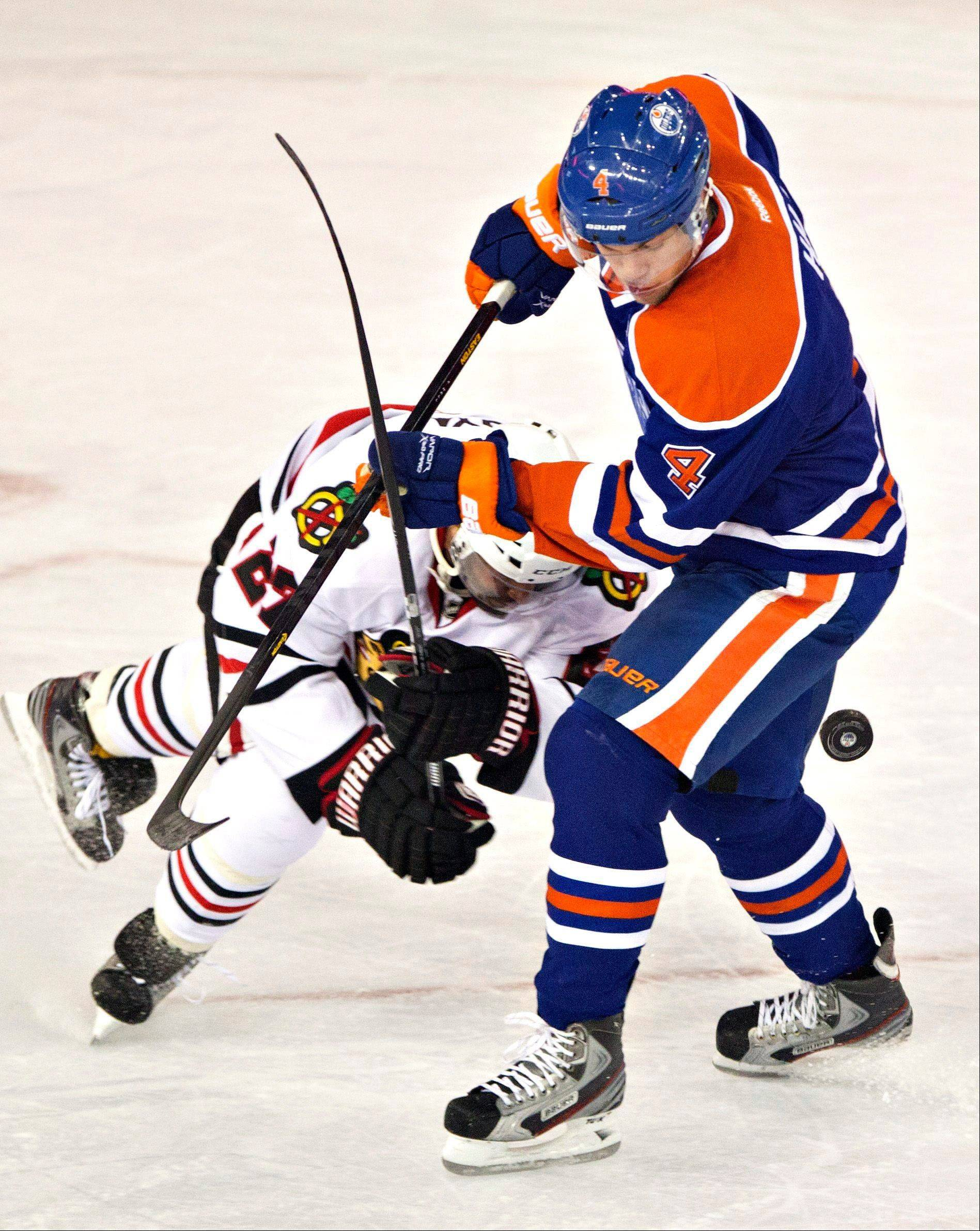 Chicago Blackhawks' Johnny Oduya is checked by Edmonton Oilers' Taylor Hall (4) during the first period of their NHL hockey game in Edmonton, Alberta, Wednesday, April 24, 2013.