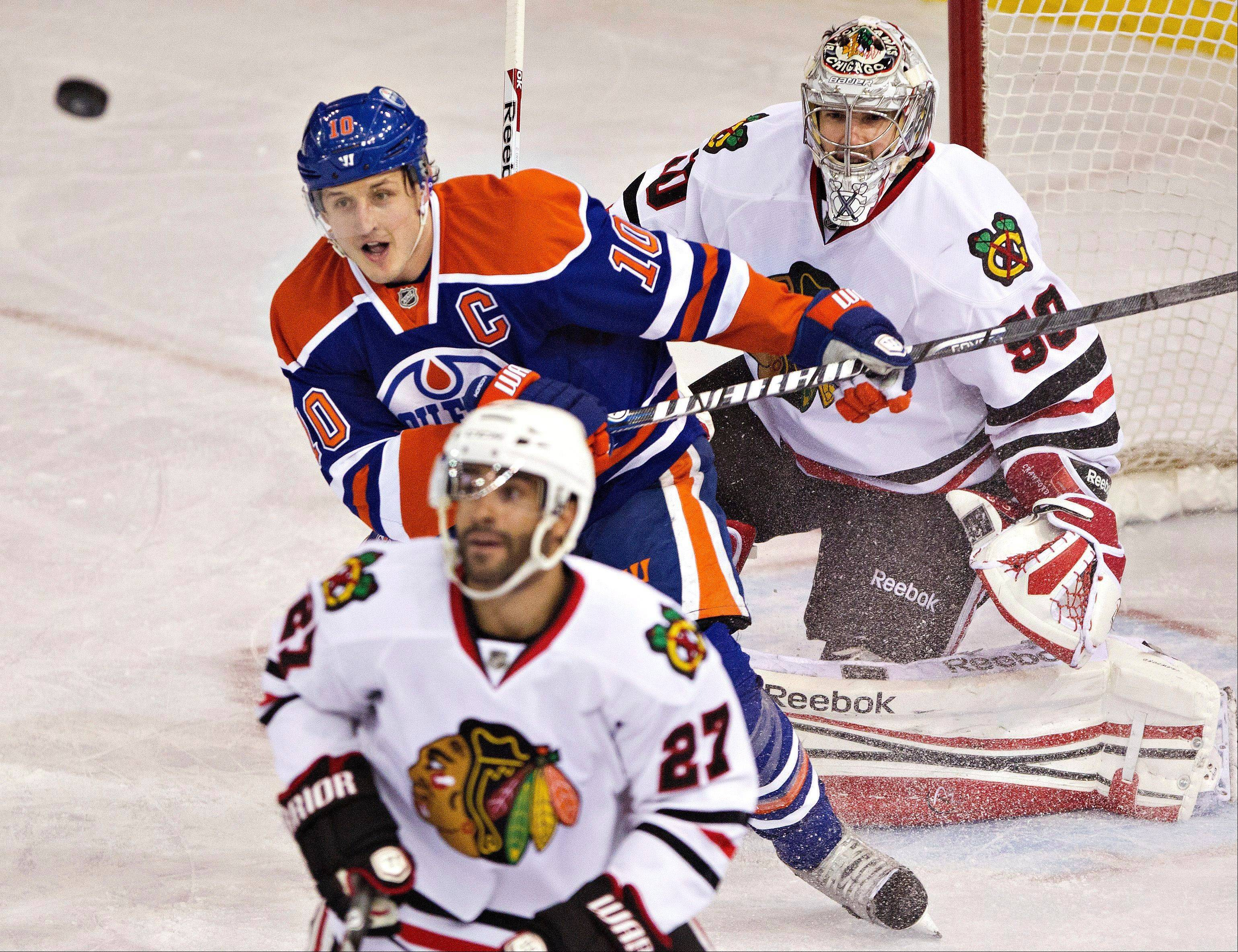 Chicago Blackhawks goalie Corey Crawford, top, Edmonton Oilers' Shawn Horcoff (10) and Blackhawks' Johnny Oduya (27) look for the rebound during the second period of their NHL hockey game in Edmonton, Alberta, Wednesday, April 24, 2013.