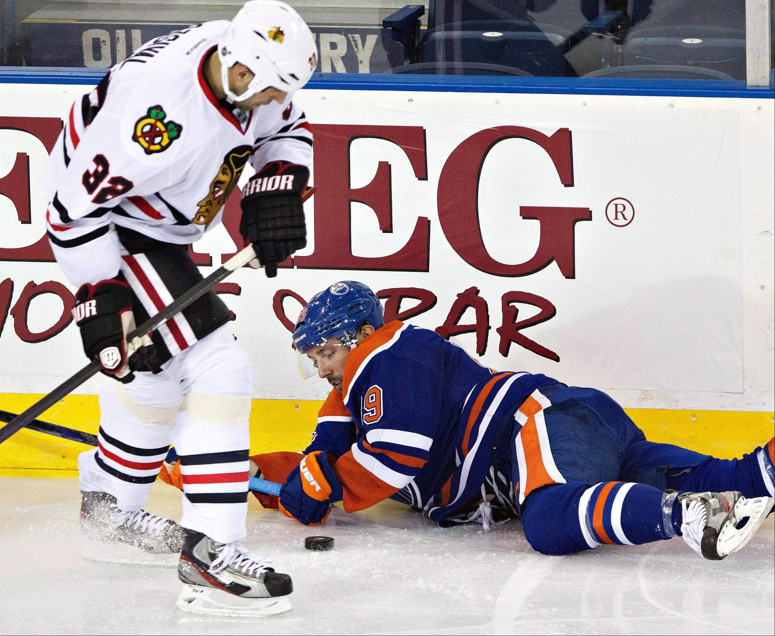 Chicago Blackhawks' Michal Rozsival, left, battles for the puck with Edmonton Oilers' Sam Gagner during the second period of their NHL hockey game in Edmonton, Alberta, Wednesday, April 24, 2013.