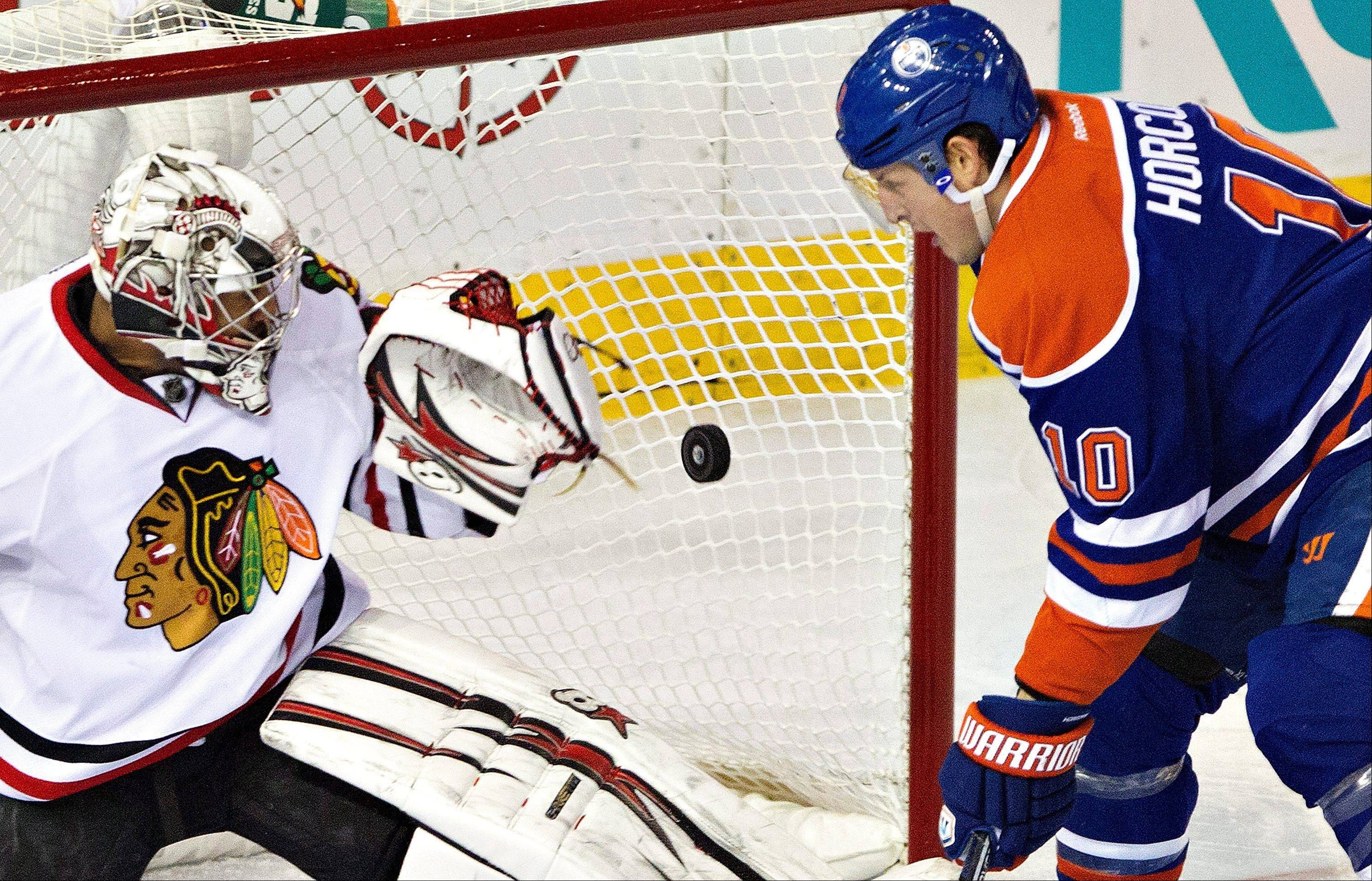 Chicago Blackhawks goalie Ray Emery is scored on as Edmonton Oilers' Shawn Horcoff, right, watches the puck go in the net during the first period of their NHL hockey game in Edmonton, Alberta, Wednesday, April 24, 2013.