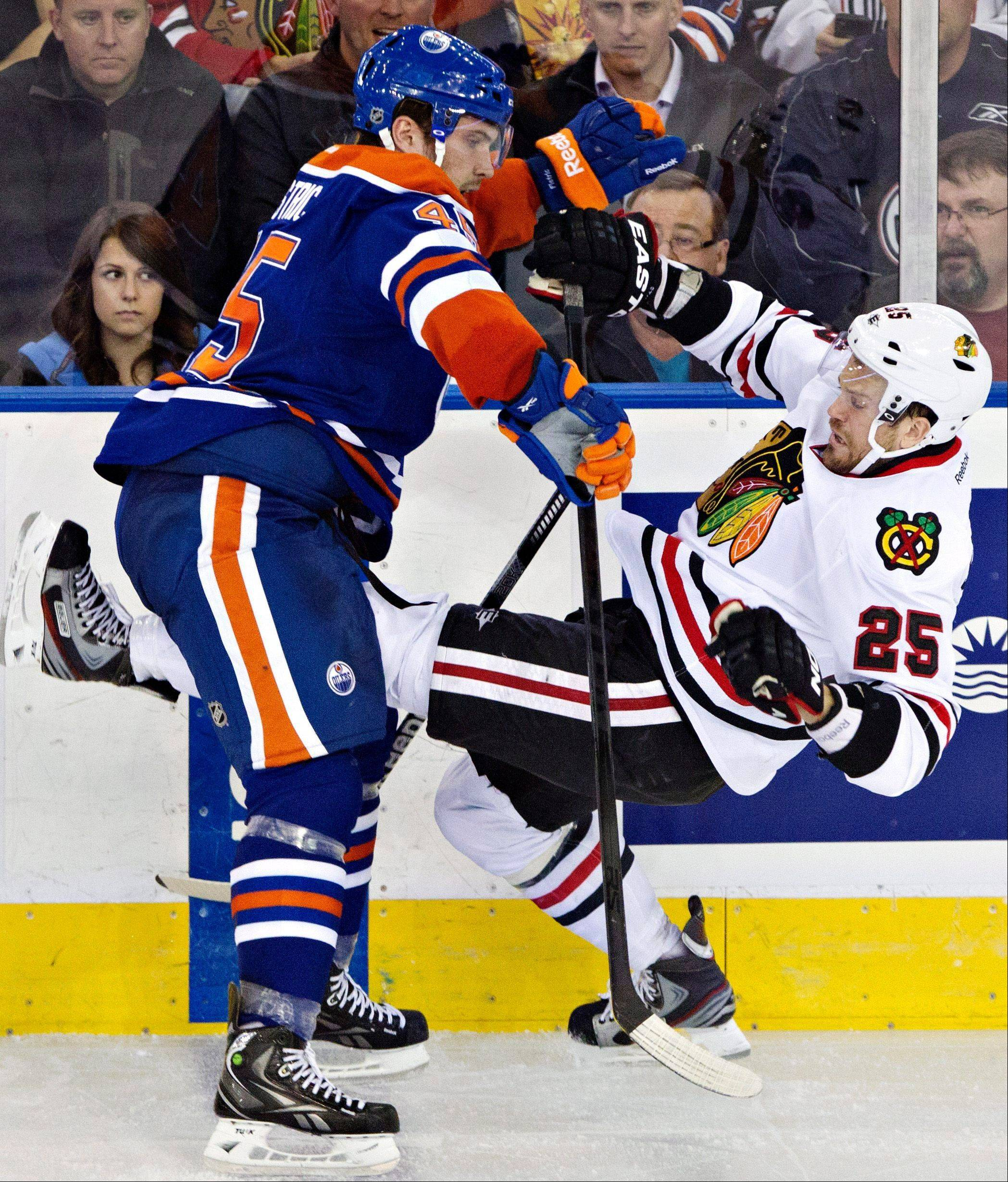 Chicago Blackhawks' Viktor Stalberg, right, is checked by Edmonton Oilers' Mark Fistric during the second period of their NHL hockey game in Edmonton, Alberta, Wednesday, April 24, 2013.